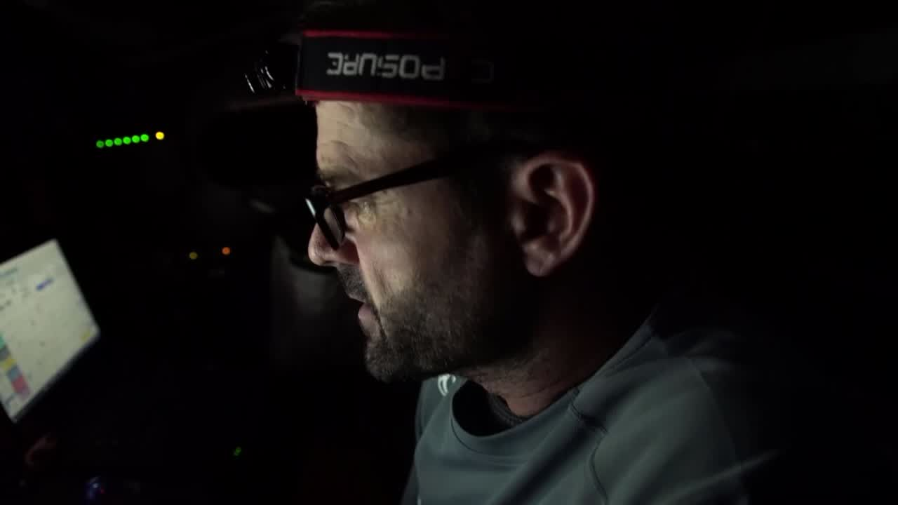 """Pascal, at nav station, is not happy. """"We lost a lot to the fleet, so not really a good choice."""" Night shots of crew gybing, grinding. Shifting the nav station below, stacking below. Pascal and Charles at the nav station, looking concerned."""