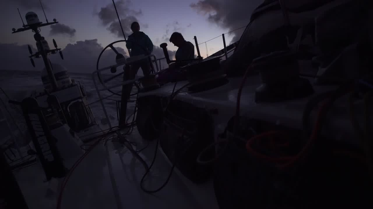 "Sunrise shot of silhouetted crew (Martine?) on the helm. Simeon at nav station, talking about their strategic moves. ""It came out well. We're in second position, behind Vestas. But it's still close racing."""
