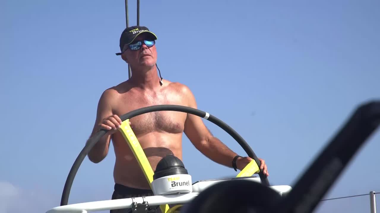 """Brunel flops with no wind. TTToP is visible to starboard. Maciel trims, talks to Bouwe on the helm. Both of them are shirtless. Maciel: """"No wind."""" Maciel talks to Martin about how some wind should fill in later from ahead of them. We see a sleeping crewmember's foot, below. Wet clothes hanging from the lifelines and laid out on deck, forward."""