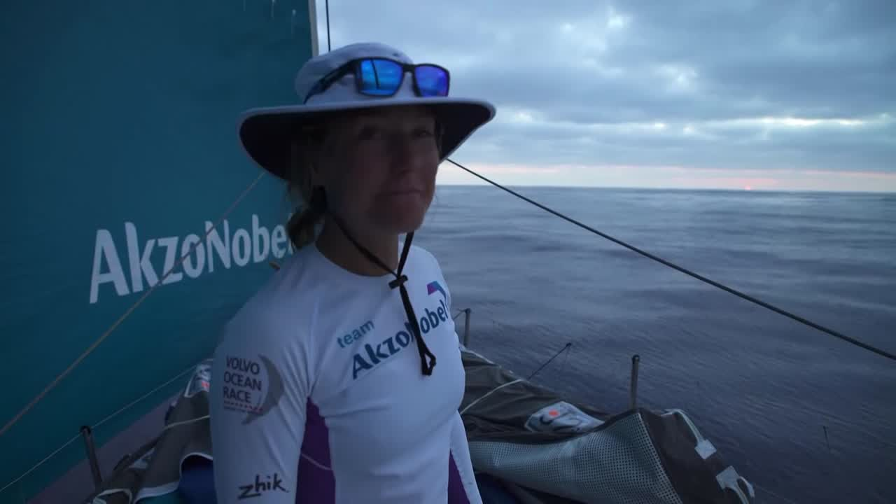 """Emily, on the bow as AkzoNobel is slatting in no wind, points forward to where you can see Porto Santo lit by the setting sun. Emily: """"Looking at where we are going, you can see the islands we've got to round, in the sunset, silhouetted."""" She grins and gives two thumbs-up to the camera."""