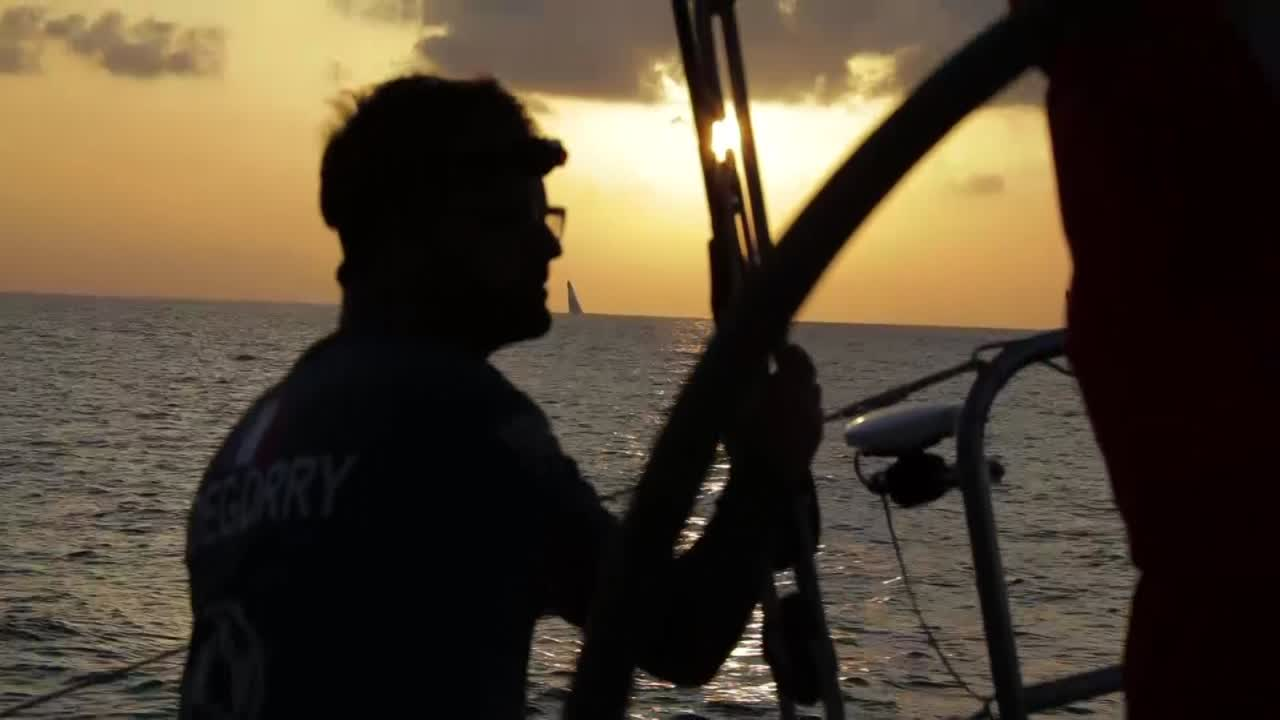 "Jérémie on the helm, silhouetted against the sunrise, with two competitors visible behind them (per the tracker, TTToP on the left and Brunel on the right). Another shot, this time of Pascal looking at the other two boats. Clew of the Masthead 0. Later in the morning, Stu talks in the cockpit: ""Battling it out for fourth through seventh here at the moment."" Stu asks Pascal, below, if he has information from the 0700 position report. Pascal responds that he does, and starts reading it out. Stu winces. Stu: ""A lot of work to do here."" Carolijn cranking a winch; Horace stacking below."