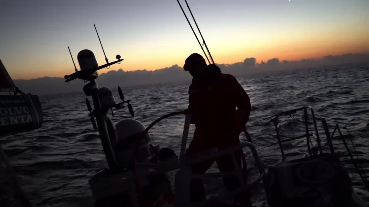 Helmsman silhouetted againt the pre-dawn with Venus. Then, in daylight, Blair talks about how they're out of the light wind and into better breeze, and about Vestas. Sunrise.