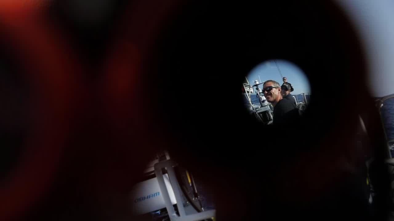 Martin shoots video of crew in the cockpit backwards through binoculars (i.e., by pointing the camera into the objective end of the binoculars), producing a vignetted fisheye effect.