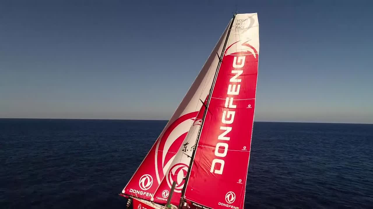A single drone shot in light winds as Dongfeng sails under Masthead 0 (I think) and staysail. Camera approaches from the port quarter at about 50 feet altitude, then rises and passes over the mastead and continues, showing an empty horizon.