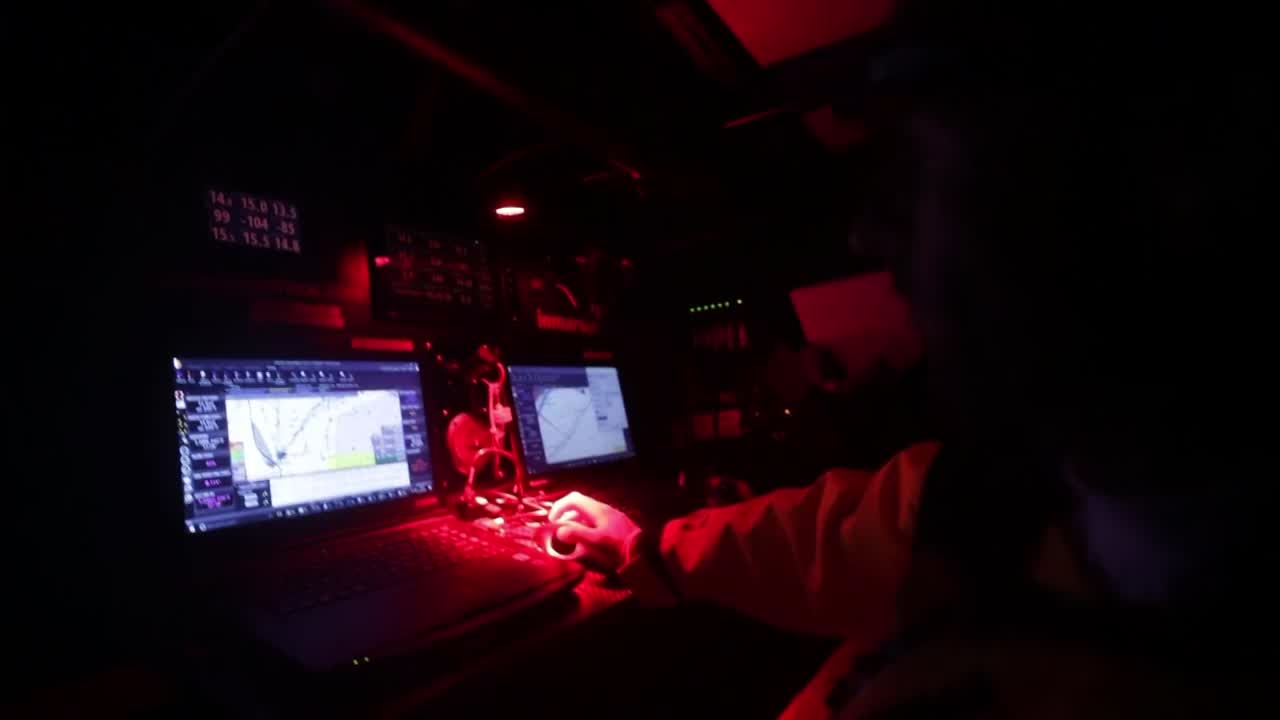 "Nicolas, at nav station at night: ""We are rounding Porto Santo, just behind Brunel and Scallywag. We are going to hoist the A3 in a few minutes, and then go to the next waypoint which is a virtual mark."" Night shot of working the pit as the sail change happens (unfurling the A3?)."