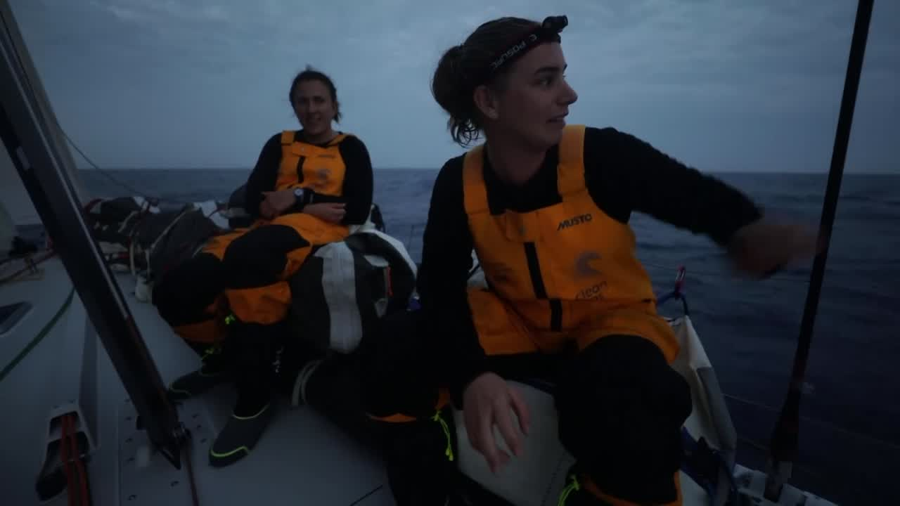 "Bianca, sitting on the weather rail with Annalise ahead of her. Bianca: ""We are heading to a palm tree in the middle of nowhere. We've got Brunel over here somewhere [gestures to starboard], a couple of other boats up in front of us... Sailing with the MH0, J3, and full main."""