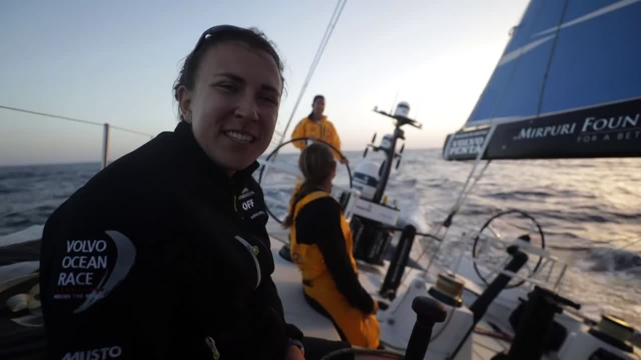 "Cockpit interviews near sunset. Annalise: ""We're having a little battle with Brunel."" Liz: Trying to get the navigator to move up the tack so she can go off watch. ""The clock is ticking..."" (taps watch). Dee laughs from the helm. Shot of Brunel on their weather quarter; Dee on the helm."