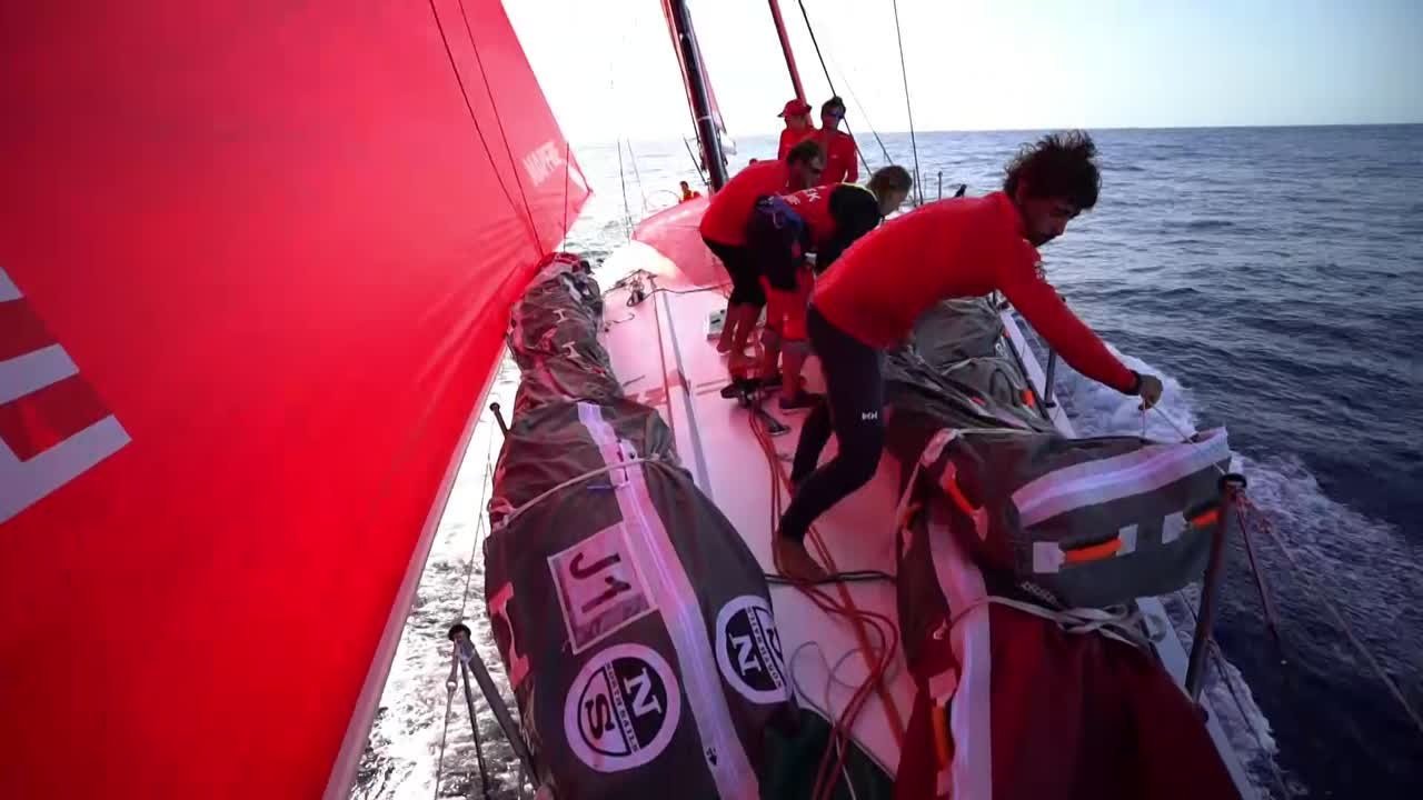 We see them tacking from port to starboard, then stacking the sails forward on the port side. Interview with Willy (in Spanish) about Dongfeng. Sunset shot of the helm; closeup of a winch being cranked.