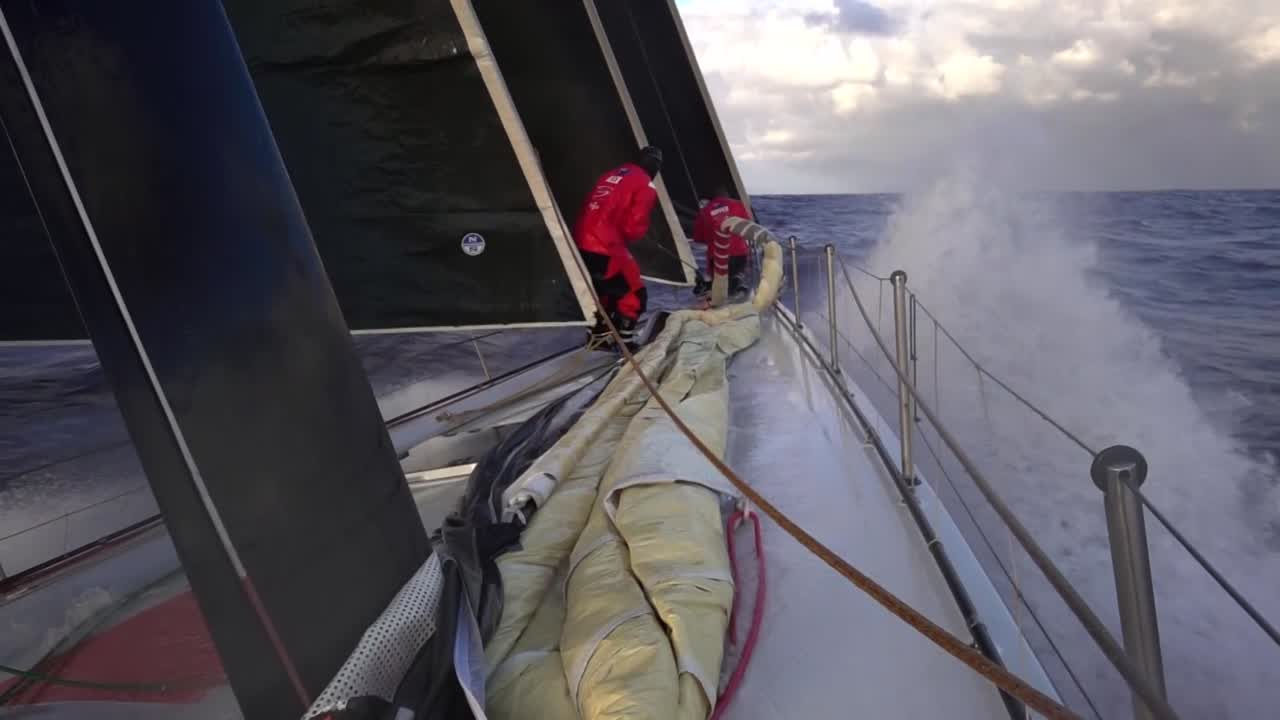 Slomo cockpit washing-machine shot with the sunrise behind them. Slomo spray on the bow as crew works the foredeck. Slomo washing machine drenching someone working in the pit.