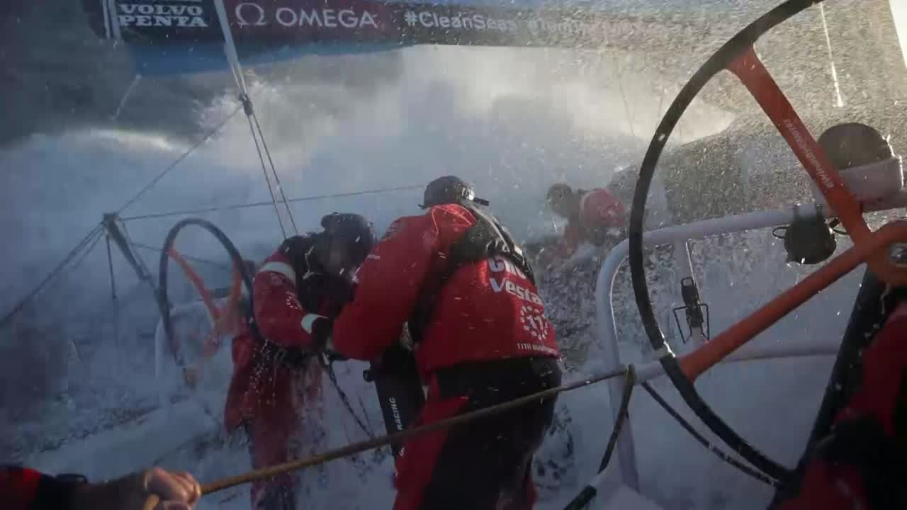 """Major washing machine as Vestas sails fast on starboard gybe toward the sunset (think this may have been from the first afternoon; this is the first video to come off the boat on Leg 2). Nick, on deck, talks about taking a break for 40 minutes. Chuny and Jena on the aft pedestal. Charlie takes spray in the face while holding the mainsheet. Someone (I think Charlie?) talks to Mark: """"Nick's working on the rudder."""" Closeup of Mark taking spray on the stern. Jena, on the mainsheet, wipes spray from her eyes. Below, Charlie (in foulies) talks to SiFi (in his bunk) about the competition. SiFi, at the nav station, talks about strategy. It's 0100, and they've been highest and fastest, but now they want to get south to avoid ending up with less wind. """"We're gonna see if we can find a faster route to the south. We've got good downwind conditions for the next 24, 48 hours and beyond... Gybing is hard work in this weather because we've got so much internal stack at the start of a leg. But that's life I guess."""" On deck in the dusk, crew shifts the stack. """"Two, six! (shift) Two, six! (shift)"""""""