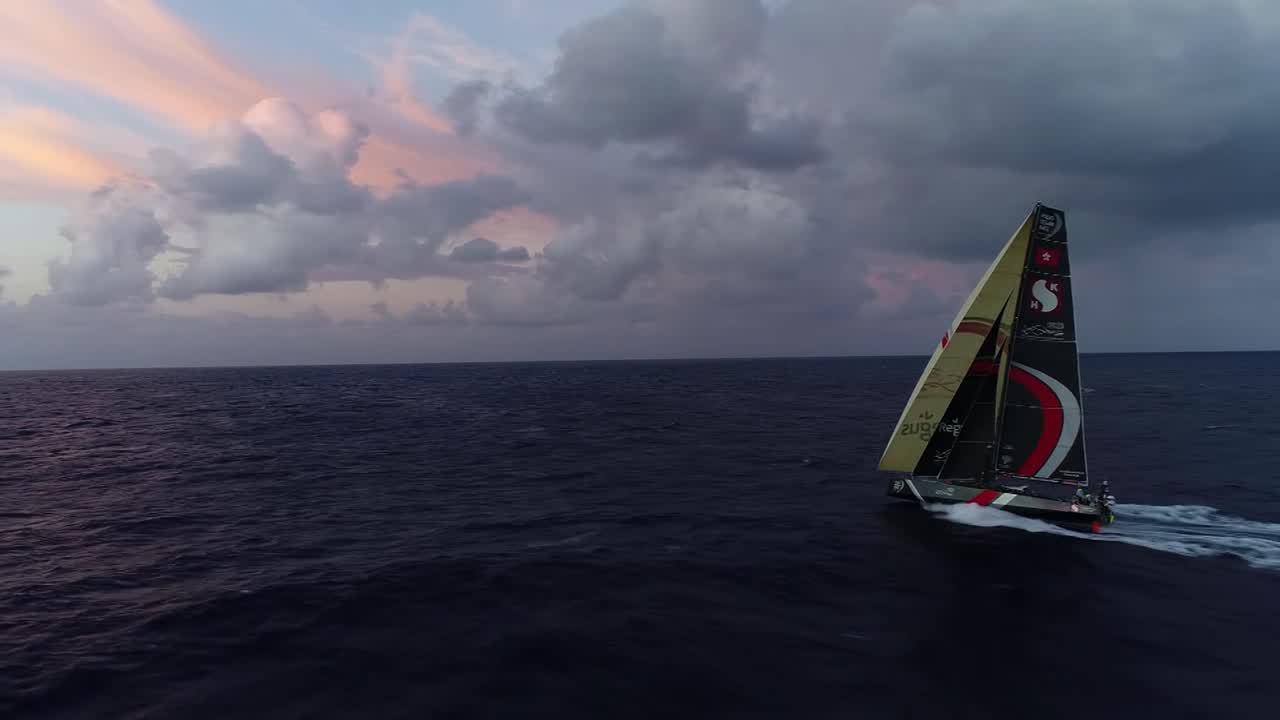 "Drone shot of Scallywag sailing on port gybe with A3, J2, and J3. Looks like it's near sunrise, with pretty clouds. Audio is Steve and Witty talking at the nav station. Witty: ""Crossing us?"" Steve: ""Not crossing us... We're probably 20 miles ahead of him?"" Steve, talking to Konrad at the nav station: ""We're being as proactive as we can, trying to be smart abou where we put the boat, but... the doldrums can create an awful lot of mixup, and for sure these leaders are going to start losing miles. So what we're losing right now, we'll definitely get back a chunk of that if not more. Basically it's two days of really keeping the faith here now. A day from now I think we'll really have a different feeling on board in that we'll be gaining rather than losing. This sort of slow, steady loss is hard for everyone on board to swallow... At the moment we're not happy with where we are, but we will make gains. There's a very long way to go in this race."" Shot of pre-dawn sky with crew silhouetted on the stern. Another drone shot like the opening shot. Witty, in cockpit: ""Every time Steven Hayles comes on deck on another sched and says we've lost they have to put their trusty Leatherman away so they don't slash their wrists. It's quite depressing for 6 to 8 hours and find out that you've lost."" Shot of Alex on the helm. Witty: ""It's not all over. There's still a bloody long way to go. As they say, 'Keep plugging away.'"" Drone shot from above."