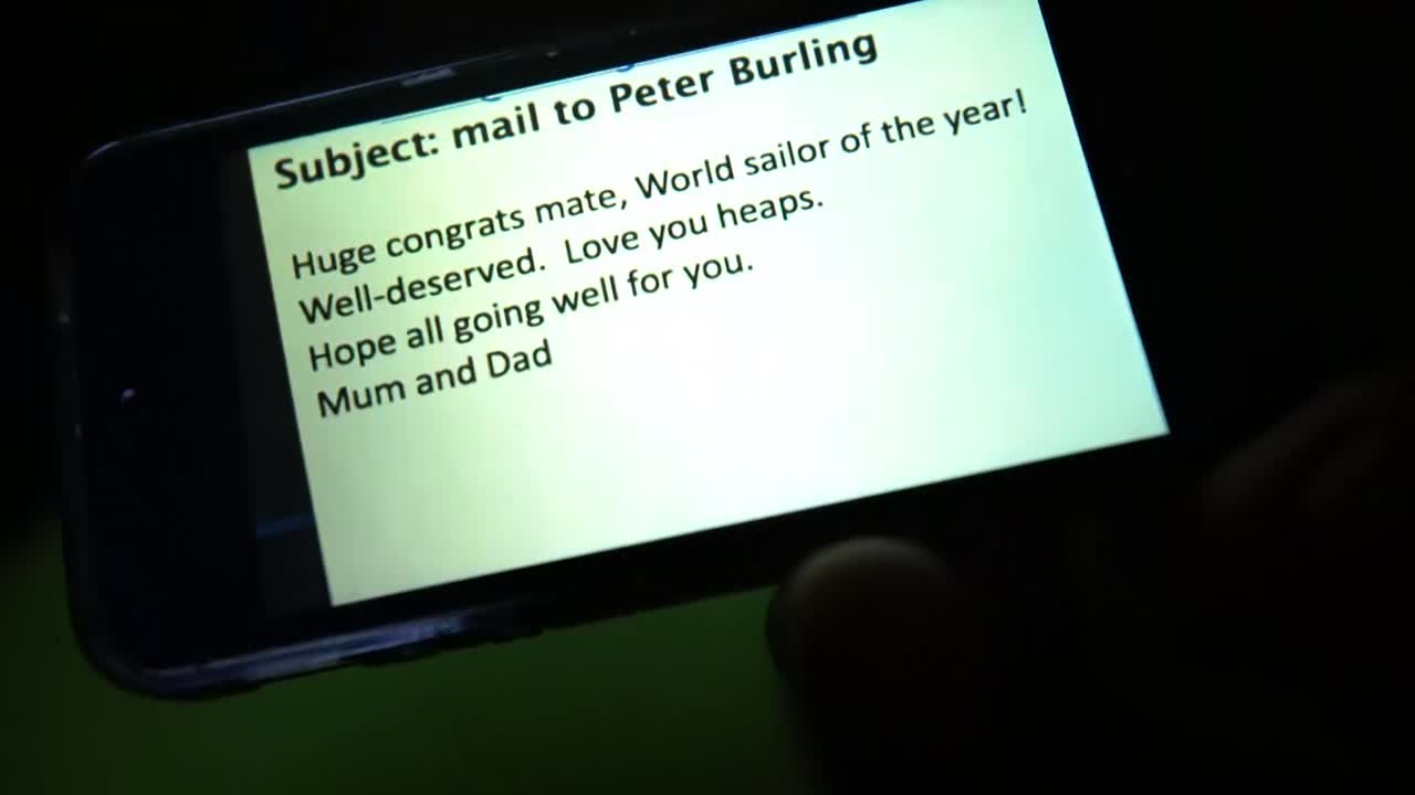 "We see the following message on a phone: ""Subject: mail to Peter Burling / Huge congrats mate, World sailor of the year! Well-deserved. Love you heaps. Hope all going well for you. Mum and Dad"" Abby, below in foulies with a headlamp on: ""We've got some great news that's just come in from Peter Burling's parents. It was World Sailor of the Year last night, and Peter has won the award. He doesn't know yet, so we're gonna go and give him the news."" On deck in the early morning, Peter is trimming the mainsheet. Abby hands him the phone. Abby: ""Read this."" Peter does, chuckles, looks around. Abby gives him a thumbs up and a clap on the shoulder, shakes his hand. Abby: ""Nice one."" Shot of Kyle on the helm with the sunrise behind him. Peter talks about the people who helped him, how he's stoked. Abby leaves. Peter: ""Part of Team New Zealand, just a small part of a 90-person team."" Keeps trimming. Not gonna get much of a reaction from him. Kyle (of Team Oracle), from the helm: ""I'm absoluetely thrilled for him. Couldn't be happier."" People laugh."