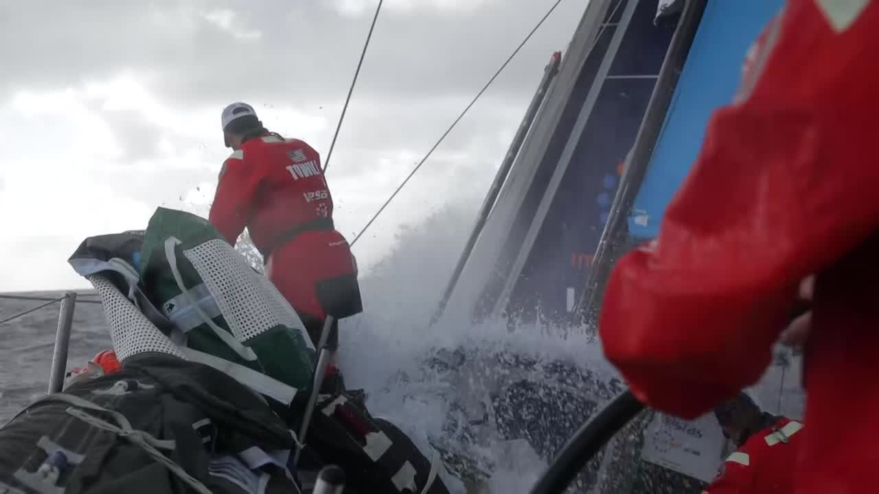 """Vestas sails fast in early morning on port gybe. Mark, on the stern: """"The night was tricky. We had a good sched in the middle of the night, we gained a bit on Dongfeng and MAPFRE and Akzo. And then the last few hours have been really tough. We've been a bit unlucky with these clouds. And MAPFRE's just behind us, they're probably less than a mile away. We were 10 miles ahead of them a few hours ago. Hasn't been the best morning for us; hopefullly we can make up for it."""" Shot of MAPFRE on their port quarter. Charlie, below: """"The cloud giveth, and the could taketh away. We did a really good job last night... riding some pressure down over the top of Dongfeng. It's been pretty random... We had a 10-mile lead on MAPFRE that we watched disintegrate in front of our eyes... It's a long leg, with a lot of ups and downs."""" Talks about """"mini doldrums"""" coming up. Shots of crew in the cockpit."""