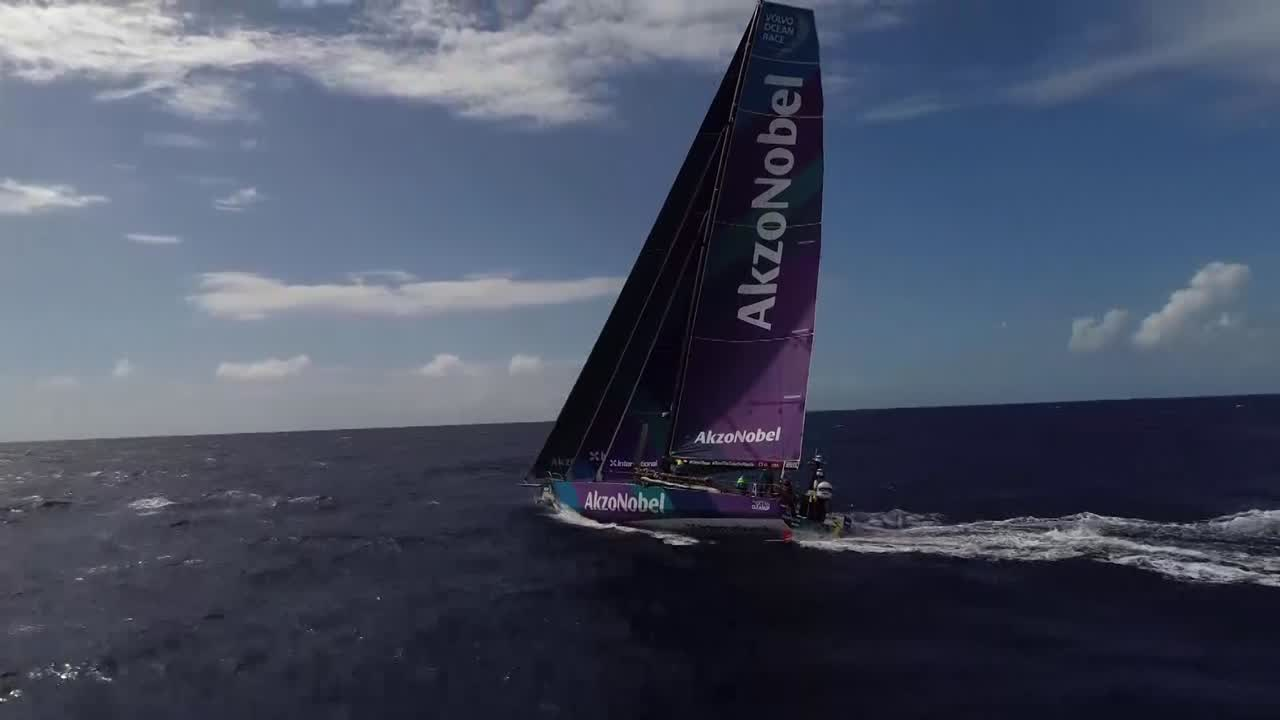 "Drone shot of AkzoNobel sailing in about 12 knots of wind, triple-heading with the Masthead 0 on port gybe. Simeon, on the mainsheet, talks about Dongfeng being visible on the horizon, talks about the bungee effect as the squalls cause big changes in the wind. Another drone shot. Jules, on the stern, talks about the wind variations and the confused seas making the boat ""like a submarine. So that's a bit hard."" Luke on the helm talks about trying to avoid nose-diving. Stern cam shot of washing machine. Brad talks about being on the mainsheet for three hours, shows his hands. ""Good for your exfoliating."" Jules talks about the wind; 23 knots at the moment, softening later. Drone shot."