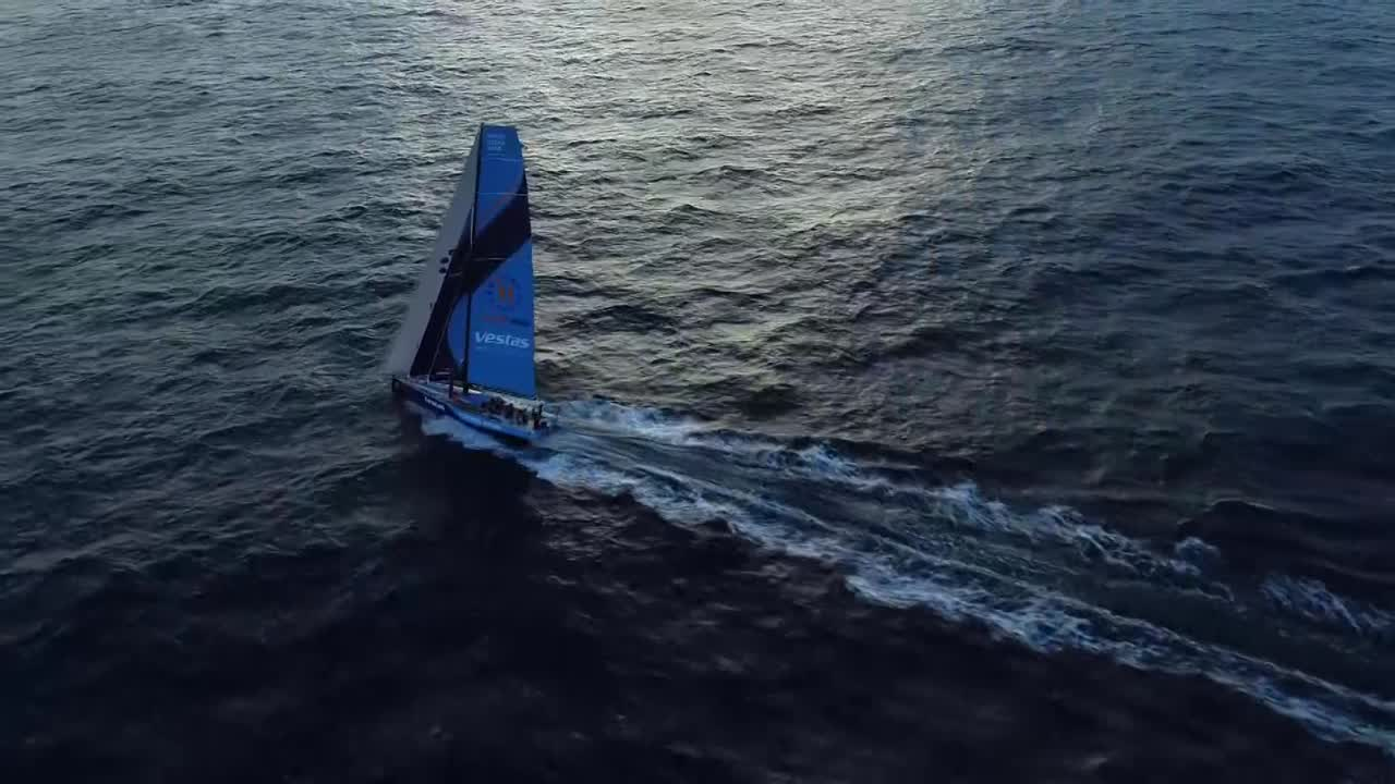 "Really pretty drone shot, approaching from high altitude as Vestas sails in about 15 knotes of wind, triple-heading with the Masthead 0 on port gybe. In the cockpit at sunset, Mark and SiFi talk with Mark (off camera) about strategy; staying to the east to get further south vs. gybing west. They know (from the 1900 sched, which presumably just came through shortly before) that Dongfeng has gybed to the west. Charlie: ""But you don't want to be soaking in 10 knots."" Mark talks to Tony Mutter, on the helm, about whether a cloud they've been watching has dissipated. Charlie, gesturing to starboard: ""I mean; we can cross MAPFRE by fucking 8 miles right now."" Discussion of the current wind direction. They decide to gybe. Includes discussion of whether to peel to the A3 as part of it; Charlie decides to wait until after the gybe. Martin asks Simon to explain; he gives a summary. They're feeling exposed being to the east of everyone; are going to gybe over to give up some lead but get further from the eventual wind shadow of the Cape Verde Islands. Below, SiFi explains to Chuy, who's getting his boots on, why the maneuver is happening. Stacey shifts her bunk to starboard. On deck, as it's getting dark, they gybe, then sail on starboard toward the sunset."