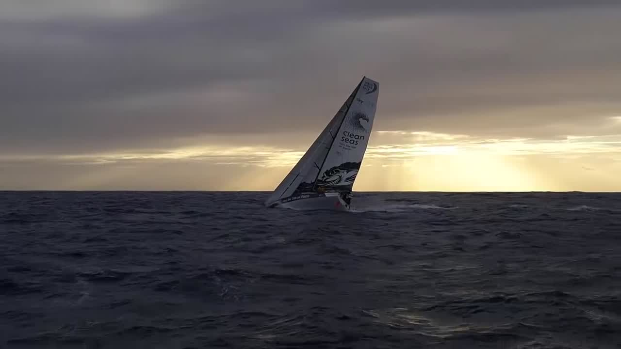 A+ drone work from drone-master Sam. High drone shot of TTToP, looking down. Fast tracking low-altitude drone shot, overtaking TTToP from their port quarter and passing astern. The boat is sailing with a lot of heel and a close reaching angle under Masthead 0 and a J3 staysail, backdropped by a beautiful sunset and crepuscular rays. Drone shot from ahead of the bow as Liz scoots out on the bowsprit and fixes some velcro fairing (?) around the tack of the Masthead 0. Shot slows to slomo as Liz looks at the drone.
