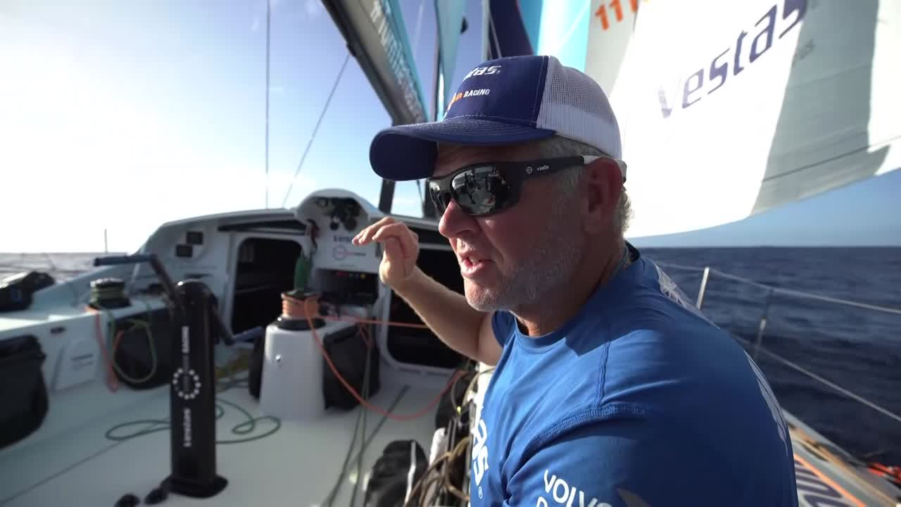 "Tony, in early morning as Vestas sails on port gybe in 7 knots of wind, explains their strategic situation: trying to avoid the cone of light wind extending from Africa, and whether to try to get south before it extends too far west, or going west to get around it. He explains where the other boats around them are: Dongfeng ahead of them going south, and Akzo and MAPFRE on their starboard quarter going west. Per the tracker, I think this must have been shot around 2017-11-09 09:35 UTC. Tony: ""It's really hard. The router says go south; the weather that we have sailing right now says go south. So that's all we can do."""