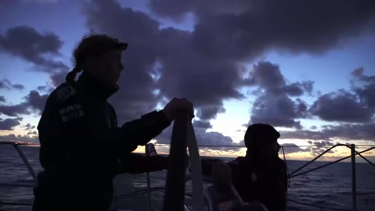 "Pretty drone shot: Scallywag reaches south on port in 10 knots of wind while silhouetted against the sunrise. Annemieke on the helm. Witty, in the cockpit, asks deadpan: ""What is stealth? Stealth bomber? Is Dee all right? Are they okay?"" Below, at the nav station, Steve explains stealth mode, and that TTToP have engaged it. Witty, below, explains the he thinks it's not a good time to have used it, since all the boats are pretty much sailing directly south in steady wind. More drone shots. Witty: ""It's a bit like poker... You need to know when to bluff and when not to bluff."""