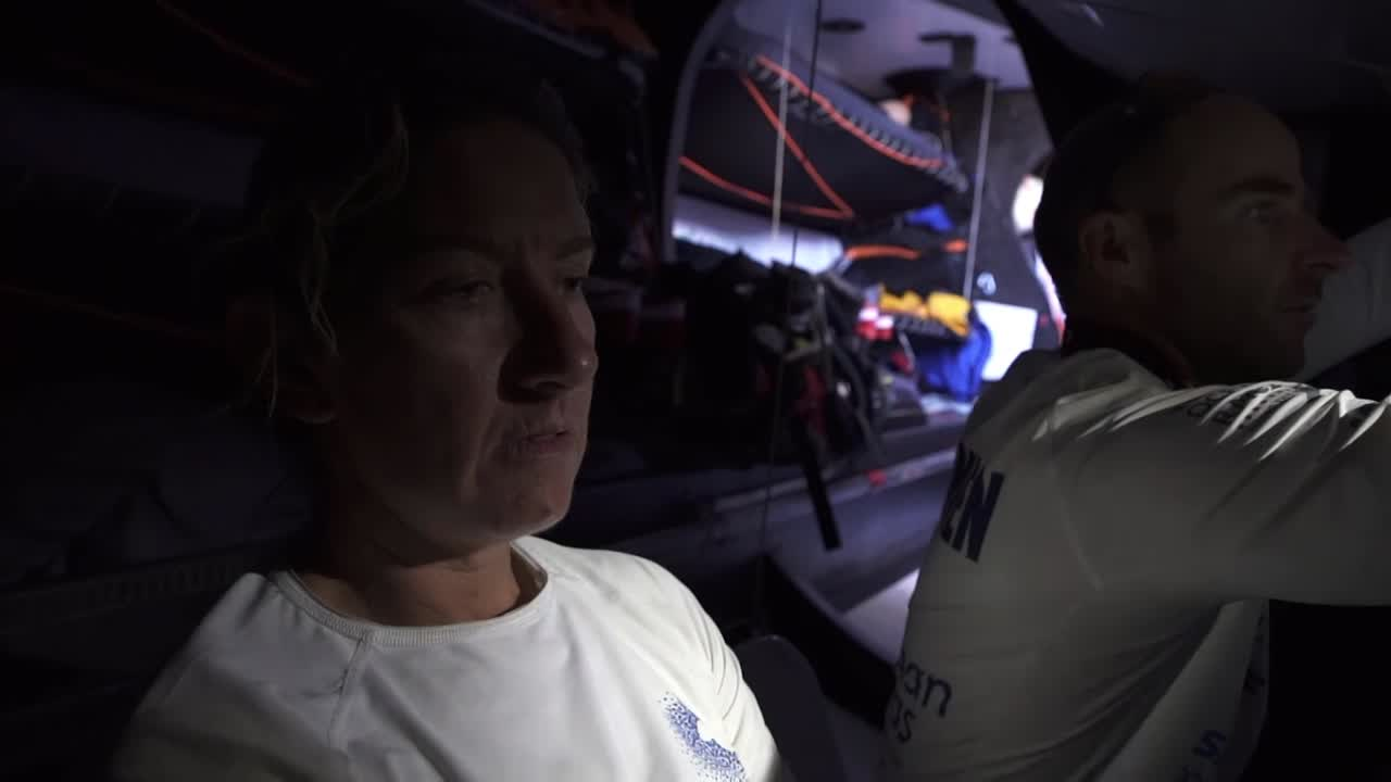 "At the nav station with Nicolas, Dee sounds morose as she recounts how they have lost ground against the leaders, who have moved into new pressure. Sam: ""In regards to our stealth experiment, how does this bode?"" Dee shrugs, grimaces. Dee: ""Hasn't really had a good effect."" On deck, talking to the crew in the cockpit. Dee shrugs. Dee: ""Bugger."" Dee, against the sky as she sits against the stack in the cockpit, talks to Sam about the strategic situation. Dee: 'It's a bit weird to be reaching. It's very unusual. I feel like we had the doldrums at the Canaries, and now we're reaching. God knews what's ahead of us."" Sam: ""And how are you feeling?"" Dee: ""A bit deflated. I'm not having a happy-Dee day today, and that hasn't really helped. But we're sailing in perfect conditions."""