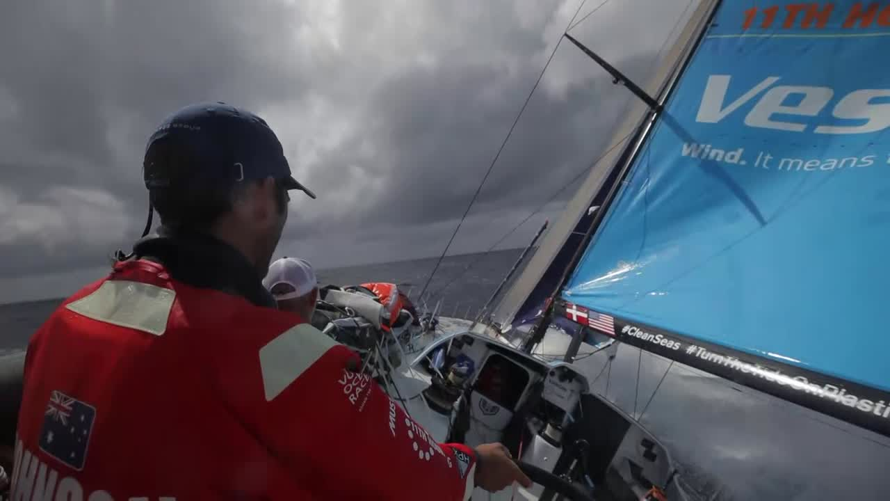"Wake shot. Shot from behind of Tom at the helm as Vestas sails reaches on port in 20 knots of wind. In the cocpit, SiFi talks about the conditions and their position entering the region normally associated with the doldrums. Behind him, Tony steers. Close up of the rudder as they sail fast. Nick goes forward to the mast as they reef the main; a wave knocks over the Martin (or at least the camera). Nick, leaning against the stack and wiping water from his face: ""Right now we're moving right along. We're coming into a cloud line and we're stuck on MAPFRE, so we're making sure we're getting every inch out of the boat."" Shot from the cabin of the pit area. Mark: ""(something) the tack down?"" Stacey works a winch. Wake shot with rain. Dark clouds behind them, with Charlie on the mainsheet and Tony on the helm. Shot looking forward from the stern as a rain squall blows over Vestas, under reefed main and J3. SiFi smiles into the camera. SiFi: ""I told you it would get harder."" Jena grinds. Jena, below, describes dealing wth the squall, with sail changes and lack of sleep."