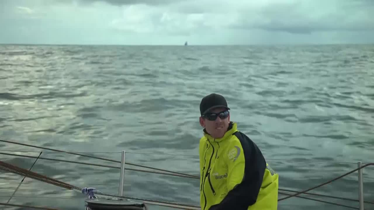 "Peter sits to leeward and calls sail trim. Beyond him we see AkzoNobel to leeward. Kyle, on the helm, talks about boats visible ahead of them. Kyle: ""Two of them. Must be MAPFRE and Vestas."" We see a distant shot of the two boats ahead of them, the boat to starboard (which I think is Vestas) more visible than the one to port (which I think is MAPFRE). Maciel stands in the forward hatch talking about the nearby competitors. Carlo, on the bow, talks about how they have the best sailor in the world (Peter) on the helm to try to catch them. Shot of Peter on the helm. Clouds ahead of them."