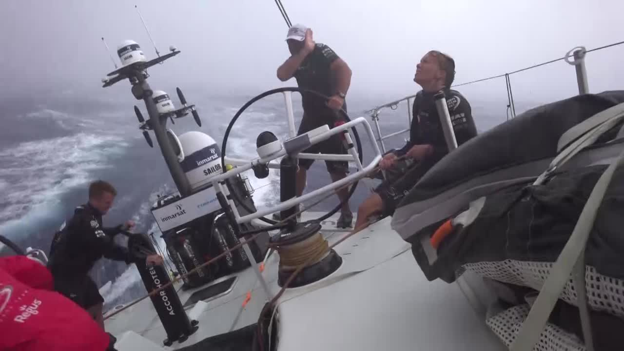 """Steve, at nav station, talks about the clouds and rain. Shot of crew grinding in the cockpit in the range. Luke, grinding: """"Almost got caught with our pants down on that one."""" Luke talks about rapid and large windspeed and direction changes. Alex: """"This is like reverse doldrums. There's been wind, but we're getting screwed by clouds all the time."""" Steve talks about the weather systems, clouds, winds, how every time is different."""