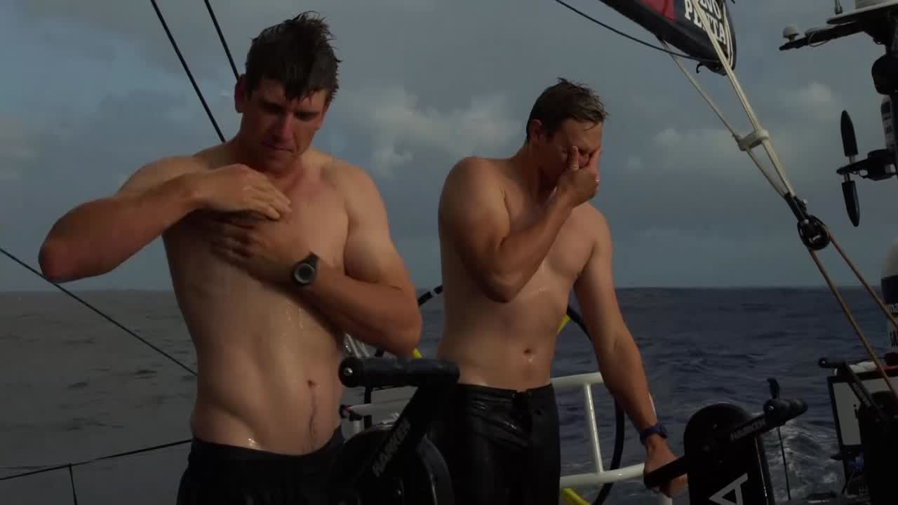 Peter, Kyle showering, shirtless, in a rain squall. Carlo working the bow.