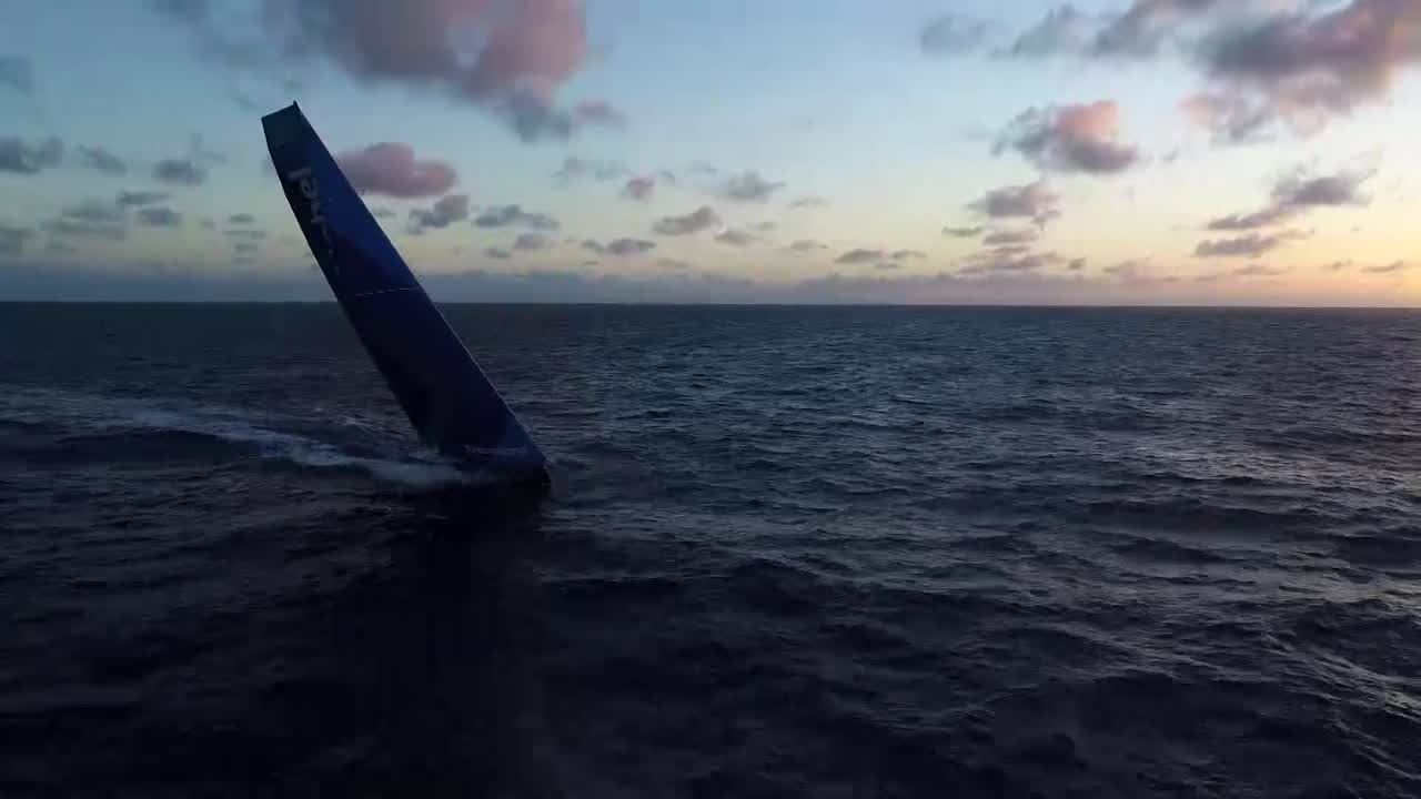 "Beautiful drone shot of AkzoNobel reaching on port at sunrise. Nicolai types at the nav station. He talks about how they just peeled to a fractional sail. Falling a little bit behind the other boats; looking for speed. Mast cam view of the deck. Jules, on deck: ""We're struggling a bit with the reaching setup; the guys in front of us stretching away from us."" On the stern, Emily washes up. Peter, on a sheet, talks about how they have some nice waves and are trying to catch most of them without getting too low. Luke talks about how it's frustrating that the rich (ahead of them) are getting richer. Brad, below, talks about the frustrations of leaders pulling away without their being close enough to see their sail setup. (Note: He has a raspberry-colored buzz cut from the equator-crossing ceremony, which didn't show up so far in a video.) Nicolai talks about working hard, not panicking, getting faster day by day. Slomo shot of Emily and Nicho working the foredeck."