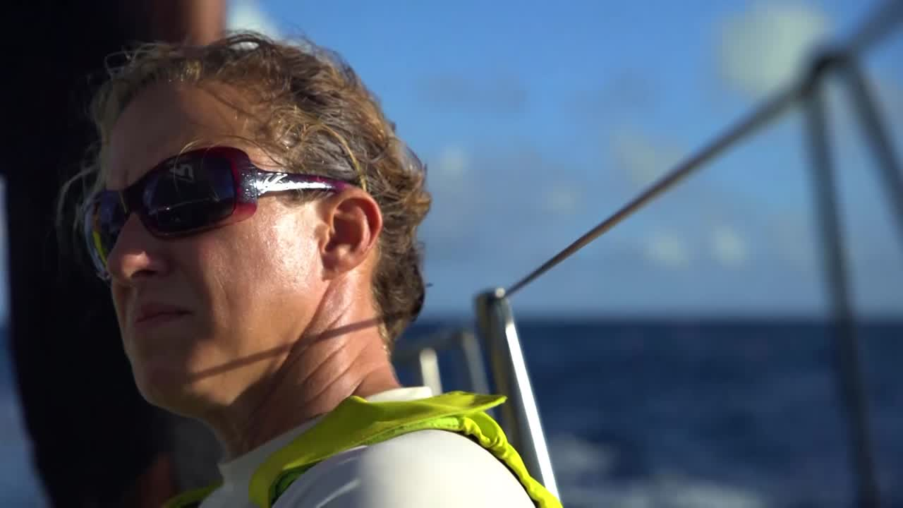 """Bouwe, on deck, talks about passing the equator and heading south in the tradewinds. Below, at the nav station, Capey talks about strategy for the south Atlantic portion of the leg: Getting south as quick as they can now, then hooking into a front. Capey: """"Last couple of hundred miles will be the decider. So that's what you've got to get in position for."""" Closeup of instruments. Hands holding a sheet. Slomo shot of Vestas a mile or two ahead of them. Slomo shot of Alberto on the low side, squinting up into the slot. Carlo working on the foredeck. Spray on the clew of a headsail. Closeup of winch turning, easing. Kyle talks about speed gains of 0.1 knot being quite significant. Artsy slomo closeups: Winch, Alberto. Below, Richard asks Capey about Vestas: """"Do we follow or do we do our own thing?"""" Capey: """"We do our own thing."""" Sunset."""