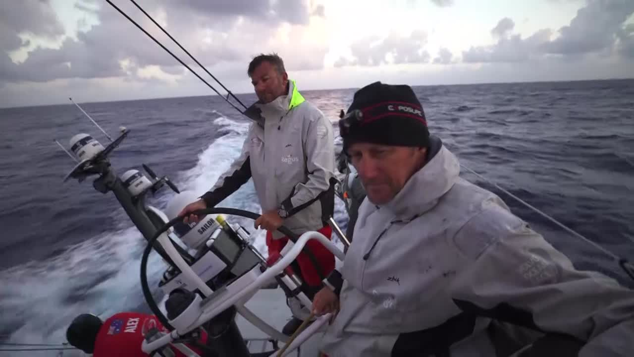 """Sunrise (wonder how many more OBRs are going to open their video with that shot?) Witty on the helm, John on the mainsheet. They seem kind of glum. Below, at the nav station, Steve talks about the sched with someone off-camera. Steve: """"We were one mile further on Akzo but they were five degrees higher, but other than that we had the equal/worse run. The Plastics have the best run again of the whole fleet."""" Steve, to Konrad: """"We had pretty good vision on them yesterday, and then they started moving really quickly. And we've just been bleeding miles to them ever since."""" Steve talks about TTToP having more people, making them heavier and that might be helpful in current reaching conditions. Witty, below, looking tired: """"We don't have enough time in the boat, sailing at certain angles. Costly lessons."""" Witty pours hot water into his insulated bowl. Witty: """"It's a new place for our team to be in, getting our head kicked in sched after sched and not really knowing how to fix it, not knowing what's wrong. Just gotta keep trying, mate. Becoming a little bit embarrassing. Hopefully the next sched will be better. Just gotta keep looking forward. Stop the bleeding, and then think about how we're going to gain. It's quite hard. Bloody hard, this race. And the opposition are bloody good."""" Oh, Witty. Don't make me have feelings for you. Witty sits at the nav station and puts on his reading glasses."""