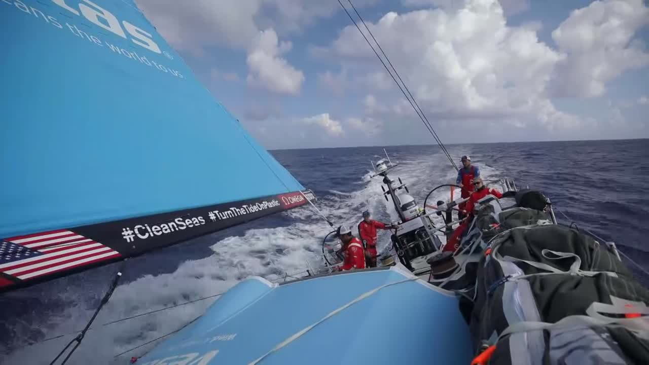 "Vestas reaches fast on port. Tony grinds the aft pedestal. Charlie steers. Mark, on the rail, talks about how they've been racing close to Brunel, but now they (Vestas) are going a little more west. (Actually, looking at the tracker, the other leading boats are on the same line with Vestas; it's Brunel who's diverging east.) SiFi, in the hatch: Talks about the cmpetition with Brunel, how they've been a little faster in these conditions. But they think they'll be faster when the angles change. Slowly diverging courses. SiFi: ""We're getting to a place where we're sailing around the South Atlantic High."" More downwind eventually. Tom, on the mainsheet, talks to Tony, on the helm. Slomo of Tom grinding."