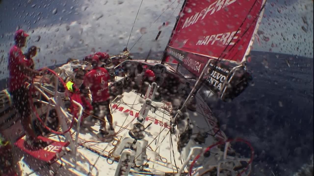"""Crash cam footage from the stern camera. We see Ugo going forward with a camera with a long lens. He sets up by the weather shrouds, shooting back toward the stern. An unexpected wave soaks him; he comes aft. Crew, laughing: """"Ugo is wet."""" """"Oh; Ugo got smashed."""" """"Ugo is wet."""" Hope his equipment was okay."""