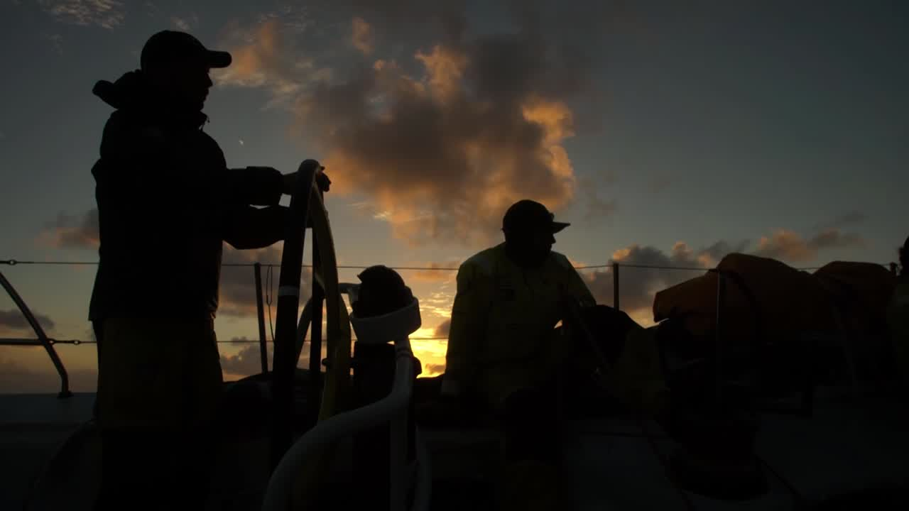 "Sunrise. (That's the fourth OBR who has started a video with the 2017-11-15 sunrise.) A crewmember looks to leeward through bright orange binoculars. Below, someone (I think Alberto?) talks below, in shadow, about having a really good 24 hours and passing Vestas. Someone (I think Peter?) wipes his face with a cloth. Capey and Bouwe sit at the nav station. Capey: ""Not bad."" He laughs. In the cockpit, Bouwe asks Maciel how far he thinks they are from Vestas. Maciel: ""Ten?"" Bouwe: ""Sixteen and a half."" Maciel, to someone asking him from out of frame: ""Three eighteen, sixteen and a half."" He points to the starboard quarter. Thinking this must have been the 2017-11-15 1900 sched? Tracker doesn't show them quite that far apart, but it's close. Below, Abby takes off her foulies. In her bunk, she talks about having MAPFRE in their sights next. Carlo works the bow for a sail change, including slomo footage. Peeling J1 to FR0, I think. Slomo of bagging the old sail. Stacking, tightening straps on the stack. Carlo below, eating. Pully with line. Slomo of Kyle on the clew. Capey talking about the clouds. Carlo, below: ""It's the best job I've ever had, mate."" Winches."