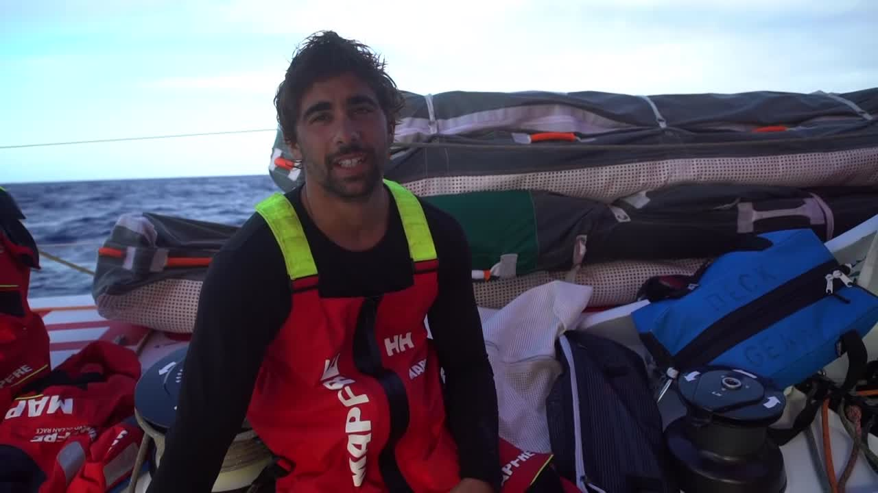 "Willy talks in Spanish: ""I miss land in general."" Rob, on the helm, talks about missing things on shore: ""Communication with the outside world, human interaction."" Támara talks in Spanish. Sophie: ""Not having any nice food, fresh food, veggies."" Xabi talks about the good sched and where they stand compared to Dongfeng and the competitors behind them. Rob talks about the hydrogenerator, how much they've been using it. Xabi and Joan at the nav station. Willy goes up the mast; shot of them grinding him up in the cockpit, him calling to them to stop. Sunset. Very-low-altitude drone shots."