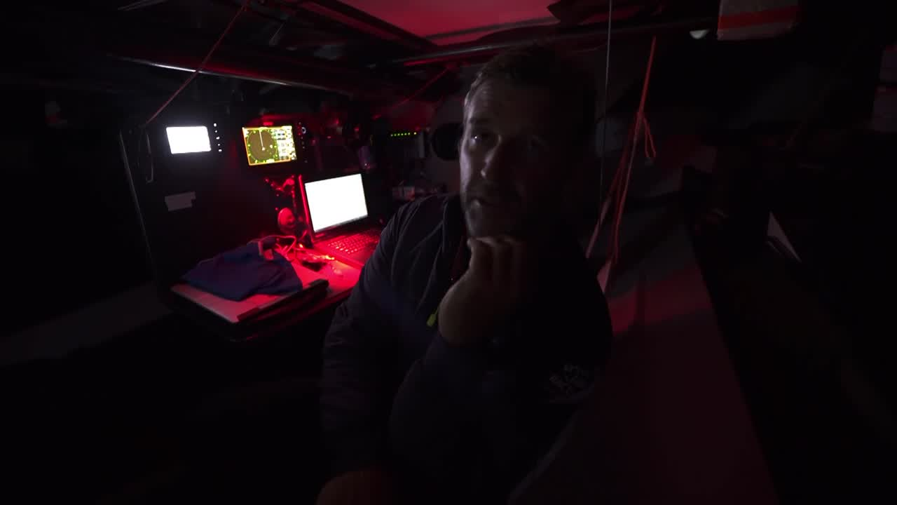 "At the nav station on port gybe, Steve talks strategy with Witty. Steve explains the strategic situation to Konrad: The boats ahead are going to be doing well against them, but they're focused on beating TTToP to the gybe. There's a call from the deck: ""They've gybed behind us guys"" and Witty and Steve immediately jump up and head on deck to gybe. We see the gybe to starboard happen from the port cabin hatch. Looks like it's fairly early in the day; I think this is the gybe that happened around 2017.11.18 07:28:10 UTC. On deck, Witty talks about strategy, and how he thinks they need to split to the west to set up for more wind later, and have a chance of catching one of the boats ahead vs. settling to just keep battling TTToP. But then he second-guesses himself, saying they've spent all this time clawing their way ahead of TTToP; it would be foolish to throw it away now with a rash decision. Shot of TTToP on port gybe behind them. Parko, standing at the forward pedestal, relaying information from below: ""Halesy really thinks we should gybe."" Witty: ""Okay; let's gybe."" Parko: ""Yeah. [turning below] Okay, we're gonna gybe Halesy!"""