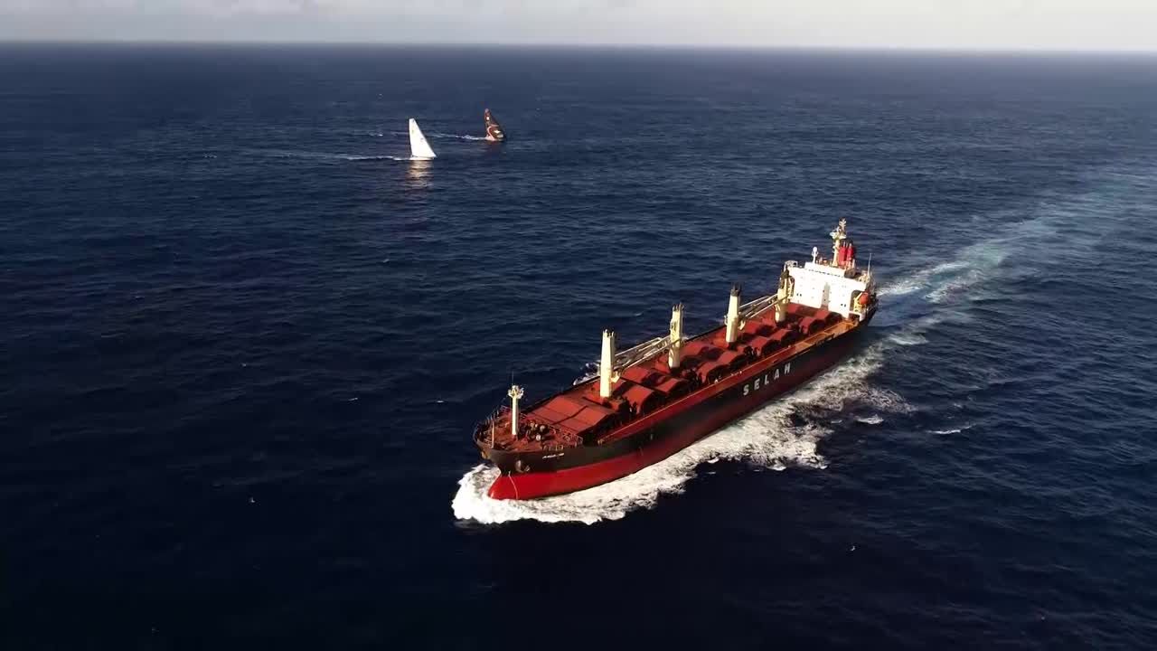 "Holy crap, what a drone sequence. Sam gets drone footage of TTToP and Scallywag sailing neck and neck a few boatlenghts apart with a crossing tanker/container ship *in the foreground*. What must they have thought on that ship? Footage in deep dusk aboard TTToP, sailing on starboard gybe, with Scallywag visible to starboard with their port red (or maybe stern white?) masthead light visible. Woman's voice on TTToP: ""They're gybing, woo!"" We see Scallywag gybe onto starboard. Then we get drone footage from ahead of Scallywag, passing back past them with TTToP a few boatlenghts behind them. Footage from TTToP with Scallywag even closer, ahead and to weather of them. High-altitude drone shot with both boats visible below and the sunrise behind them. Liz, on the helm, in the morning light. Sam asks her what's happening. She explains that Scallywag gybed to windward of them, trying to get through them, can't get through and waiting for a lift. Liz: ""We're just trying to stay as close to transom of them as possible so they don't get away. Every time they've come within distance we've let them get away, so we're determined to keep them this time."""