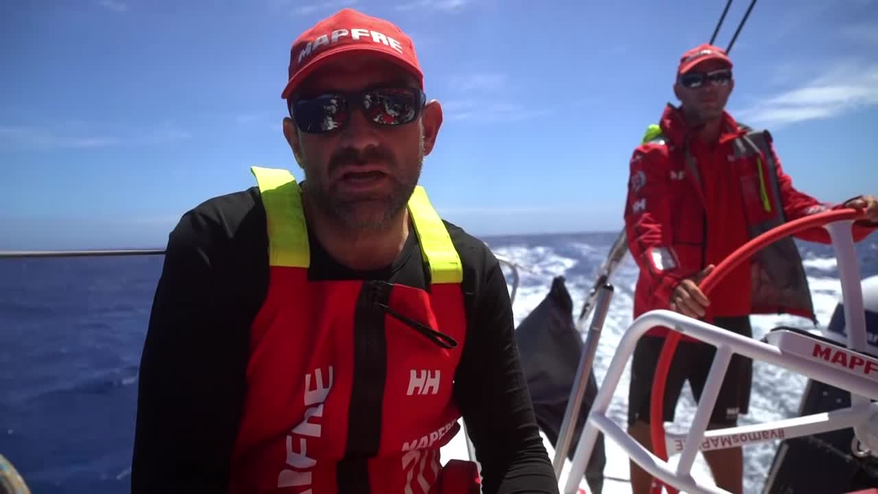 MAPFRE sails on starboard gybe. Xabi talks about how they've been sailing around the St. Helena high, and last night gybed [to starboard] to go southwest to hook into the front and head for Cape Town. Ñeti, trimming the main, talks in Spanish about where the other boats are. Xabi says he thinks they have a good position despite gybing quite early. He and Rob talk about the other competitors' positions relative to them in the latest sched. Joan reads from the tablet, telling Rob, on the helm, where the other boats are. Joan talks in Spanish about the other boats. Sunrise. Sophie trimming the main. Blair and Xabi grinding. Shifting the stack. Shot of the bow as they are triple-heading on starboard. Translations here: https://youtu.be/LqY11k_IjCI.