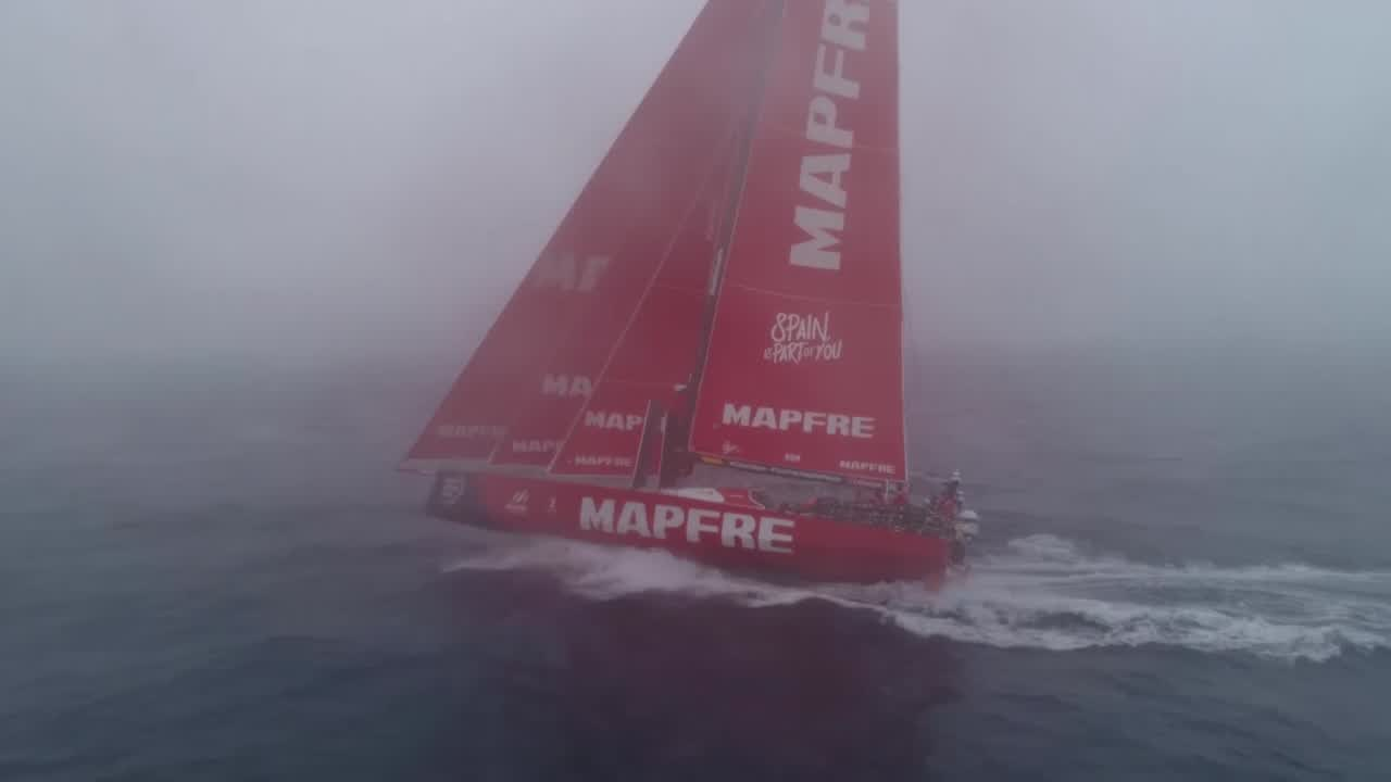 Drone footage of MAPFRE sailing in fog. They're on port in about 10 knots of wind, triple-heading with the MH0. Sped-up drone footage that transitions to slomo as the boat passes the drone. Drone shot of the stern, someone (I think maybe Ñeti?) waves.