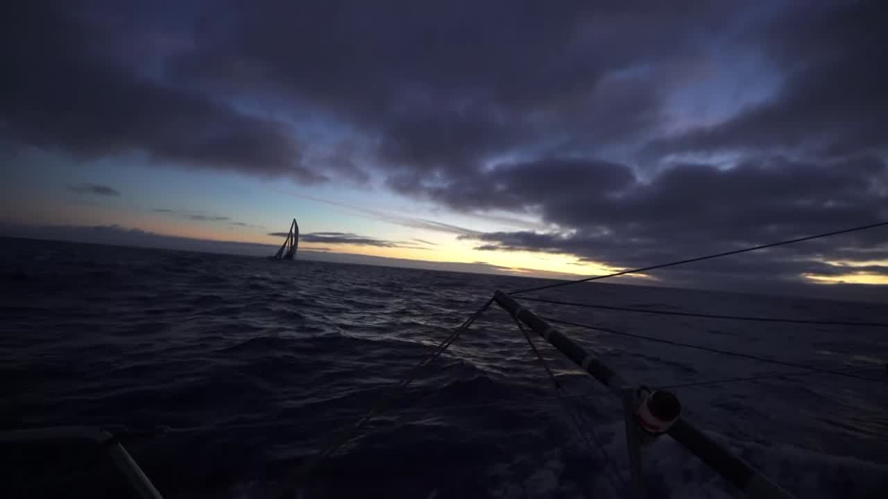 "TTToP, sailing on starboard gybe, is silhouetted against the dawn as they approach Scallywag, on port. Scallywag gybes in front of TTToP. (Same gybe we saw from TTToP's perspective in their video from 08:40:01 today.) Steve, with TTToP visible a few boatlengths behind them: ""Sort of can't shake them off at the moment; they keep coming at us. But that's all right. It's good two-boat testing."" Witty, on the helm, looks over his shoulder at TTToP even closer behind them. Steve talks about how when they were reaching toward Cape Town it was easier. Now, running, the strategy is more difficult. He explains that they're both sailing away from Cape Town at the moment, and TTToP is technically closer to the finish than they are. Steve: ""Technically they're ahead of us. Which seems a bit bizarre."" Awesome first-light drone shot from astern of TTToP looking forward to see both boats. Steve: ""There's a very clichéd saying in sailing, boatspeed makes you a tactical genius. And it does. If I can sail away from these guys it's not that hard. If we were a little bit quicker, my job becomes quite easy."" More awesome two-boat sunrise drone shots."