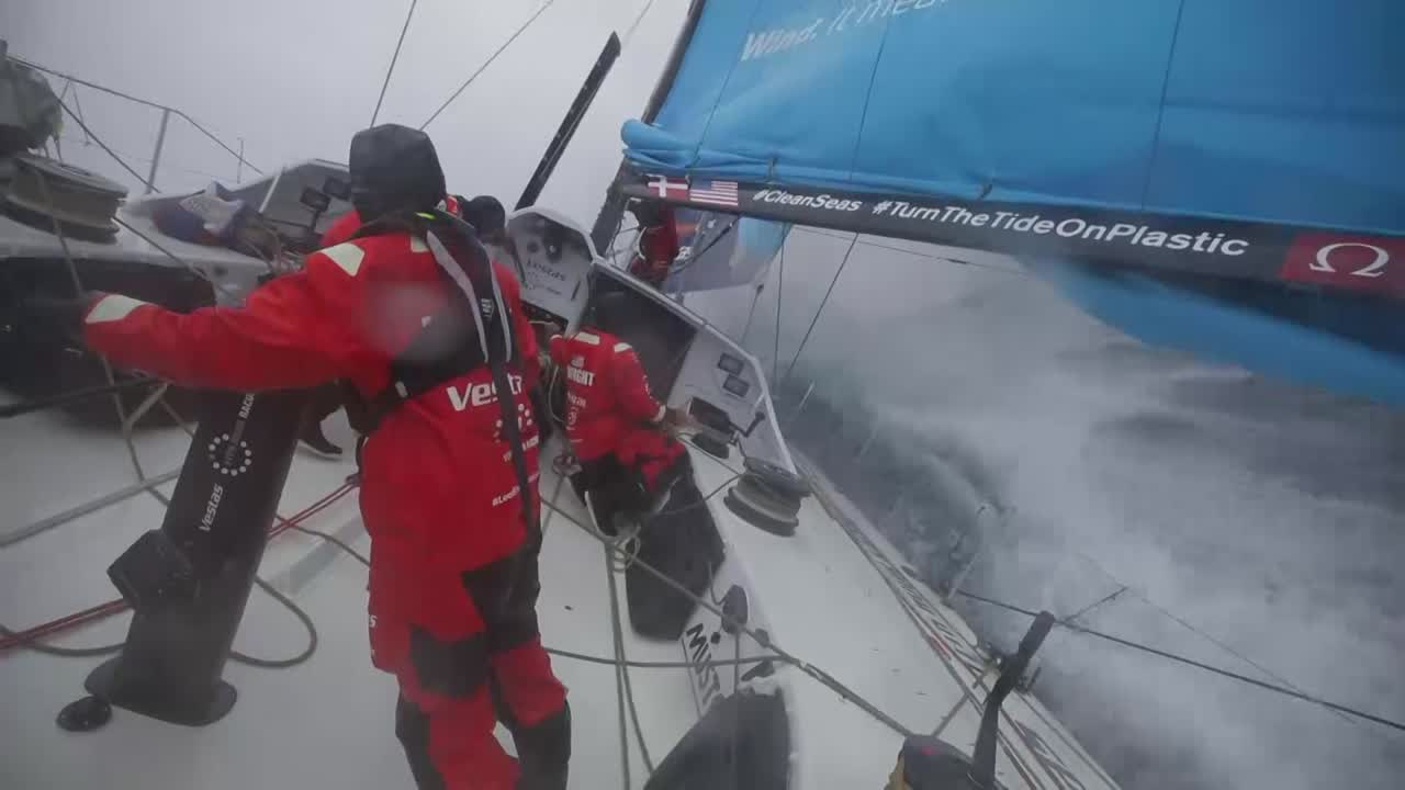 "View forward from stern as Vestas surfs in southern ocean conditions on port gybe. Washing machine. Below, at nav station, SiFi talks about the competition and strategy. Wind is lifting, and they're going to point further north. Talks about Dongfeng and MAPFRE. High pressure looks a little better (i.e., more wind). Re: MAPFRE and Dongfeng: ""Not really a surpirse to see the two most experienced boats going well in these conditions. We're learning all the time, we're pushing hard. We'll keep pushing until the weather eases off, and hopefully that way have a go at them in the last few days."" Loud, scary sound mix as we see mast cam shots of the cockpit, bow cam looking aft, fisheye mast cam looking down."