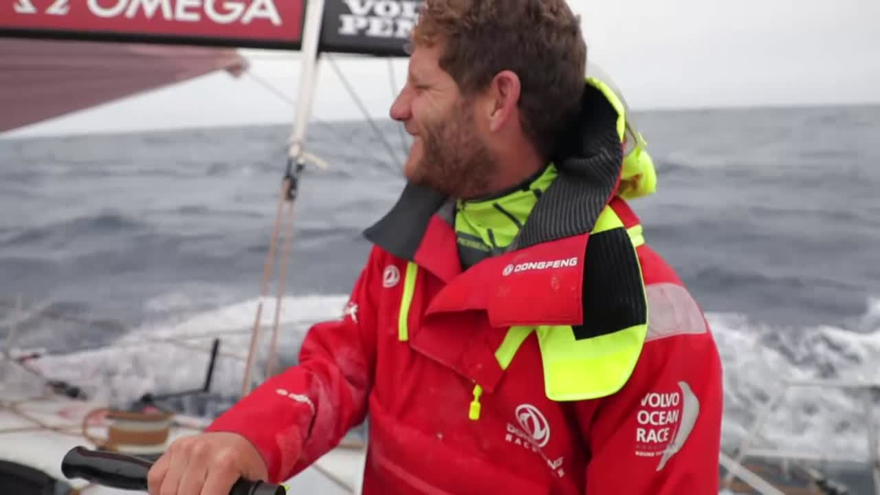 "In the cockpit, Charles talks in French. Below, Stu talks about how obviously they're pretty disappointed to have fallen behind from the controlling position, but hard work has gotten them back into it. ""Got a real race on our hands with Vestas, who are just a few miles behind us. And MAPFRE, a decent chunk ahead but certainly not out of touch."" Charles talks about Table Mountain, and its effect on the wind. Carolijn, below: ""When everything's against us is when we get the best out of ourselves and push really hard. Marie: ""As Pascal [said], we have to be faster and lower."" Stu: ""We have to remain positive and keep chipping away."" Slomo shots of the cockpit, washing machine. Darryl laughing at the pedestal, on the bow. Wake. Below, a loud sound of a sheet being eased. Stu: ""A minor wind check; nothing to be concerned about."" mast cam view of the deck, spray."