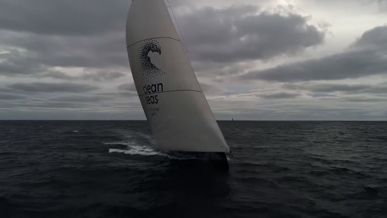 "Drone shot of TTToP sailing on port under the MH0 with low clouds behind. On the horizon behind them and to weather we can see Scallywag. Off-camera, we hear Sam: ""Hey Dee."" ""Yeah?"" ""Twenty days, how many thousand miles, you've got a race for 5th place. What's going on?"" Dee: ""It's cool..."" We see Dee talking in the cockpit. ""There actually hasn't been a day in the southern ocean when we haven't had a boat in sight or on AIS. It's awesome racing."" Liz, on the helm, talks about how long they've been fighting with Scallywag and now fighting with AkzoNobel. High drone shot of TTToP sailing away. Henry, below and looking out the hatch, smiles as the crew in the cockpit cheers. Henry: ""That is the level of excitement we get every single time we get a good half-hour average."" He talks about the tight group of three boats and how the whole leg will come down to this for them. High drone shot. Henry: ""Boatspeed. Boatspeed, boatspeed, boatspeed."" Liz, on the helm: ""Nobody wants to come in last."" Dee, pointing ahead: ""I want to take them [she points aft] and leave them behind."" Shot of the cockpit. Drone shot of the top of the rig, flying in close. Someone (Annalise?) standing in the hatch waves to the drone, then points forward. The drone pulls back and climbs."