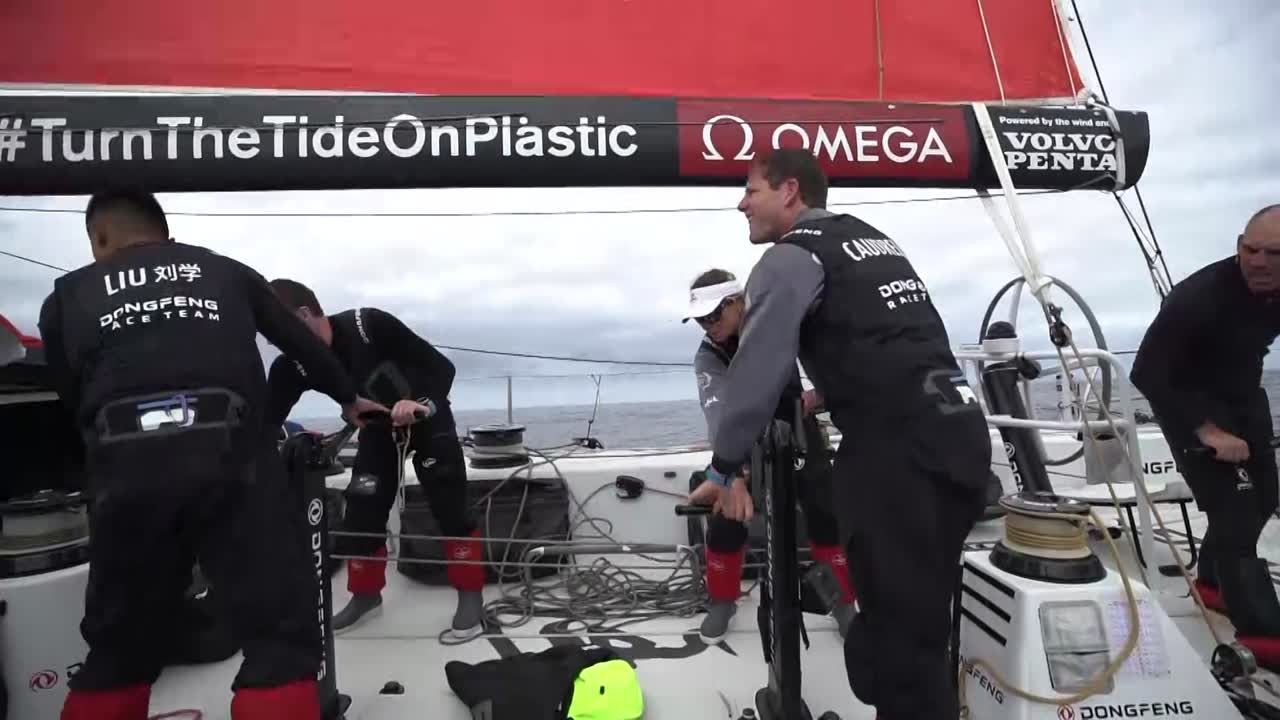 "Dongfeng slats in light winds. Carolijn calls as someone else pulls in a line: ""3, 2, 1, okay; hold furl."" Charles, sitting at a winch, says something about using the ""masthead upwind"" (MH0?). The crew trims the MH0 in light winds. Charles, holding the main steady by hanging onto a thin cable under the boom, talks about having to cross a ridge, a position in high pressure between two winds. Trying to catch the low pressure in the south. Always difficult. ""The wind is very shifty, very light, but we are lucky because the system is moving in the right direction."" Drone shot of Dongfeng sailing upwind on starboard under the MH0 with another boat (I think Brunel around 2017.12.11 09:55:35 UTC) behind and to weather of them. As the drone circles htem another boat is barely visible further away behind and to leeward of them; I think that's Scallywag. As the shot continues we see Jack going up the mast. He reaches the masthead and the camera circles him, showing the two boats shown before and then showing another boat ahead of them (MAPFRE, then the lead boat). On deck, Jack explains that in the big winds the day before part of the wind sensor unit at the masthead blew off, so he was up there replacing it. ""There's not much wind but we're right into the swell. On deck it feels really flat but when you get up there it's exaggerated by a lot. Feels like you're gonna get thrown off every three seconds. Bear-hugging it the whole time. It's really not fun. Nearly got it done."""