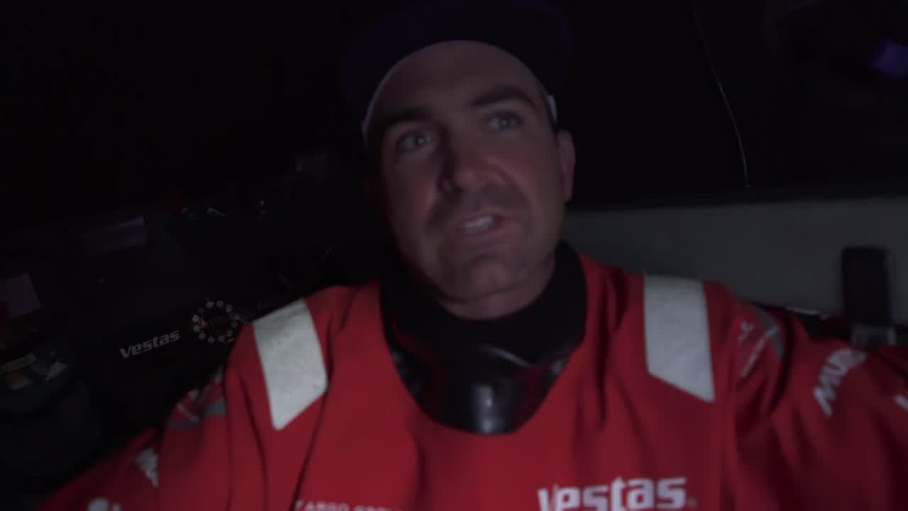 "Drone shot of Vestas with the sun low behind them reaching in 15 knots of wind on starboard tack. (Think this is from late in the day on 2017-12-11.) Charlie, below, talks about the race so far. The plan they had when they left was not the best one, which put them on the back foot. ""We've hit the reset button in the ridge."" Simon, at the nav station, says they've just had the 0700 sched, and they look pretty good. He points out their position vs. the other boats: Scallywag, TTToP, then the other pack of boats about 20 miles south. Good to be further north. In 24, 48 hours it's good to be further north. ""Certainly a more seamanlike [i.e., safety-conscious] way to go about it."" Charlie, below, talks about ""the weather, Friday, looks pretty fresh with nowhere to run."" Setting yourself to be in the right place in three days' time in 50 knots of wind is more important. Simon shows the scary low on the computer forecast. Have to be careful to not get into a position where the wind and sea state are so bad you're pushed against the ice gate and have to slow down. Charlie: ""Have to watch the weather pretty closely to make sure we don't find ourselves in a bad spot."" Drone shot from ahead with the sunset behind them."