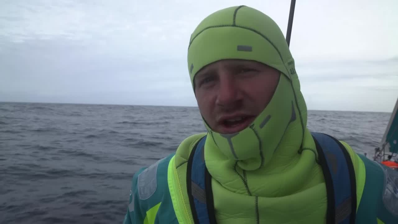 "Nicolai, on deck in his neoprene cowl in fairly light air, talks about how they're the most southern boat right now, and have just gybed. Fleet split into two groups; they're wth MAPFRE and Dongfeng. Below, Martine (in cornrows) bails out water. Jules and Nicho, at the nav station, look at routing software. Jules talks about being a bit disappointed in the latest sched, vs. MAPFRE and Dongfeng, Brunel. Nicho: ""We coughed it up there last night."" Separately, Nicho talks about how each of the boats separated; probably due to breeze. Shot of Simeon on the helm, scowling in his cold-weather cowl. Álex, in the cockpit, talks about how we are here, in the Southern Ocean, but it isn't normal conditions. ""Like a pit stop before the next depression comes, with 35, 40 knots, straight to Melbourne."" Nicolai talks about how variable the Southern Ocean is. ""It's like a spring day in Denmark up north. So I'm enjoying it."""