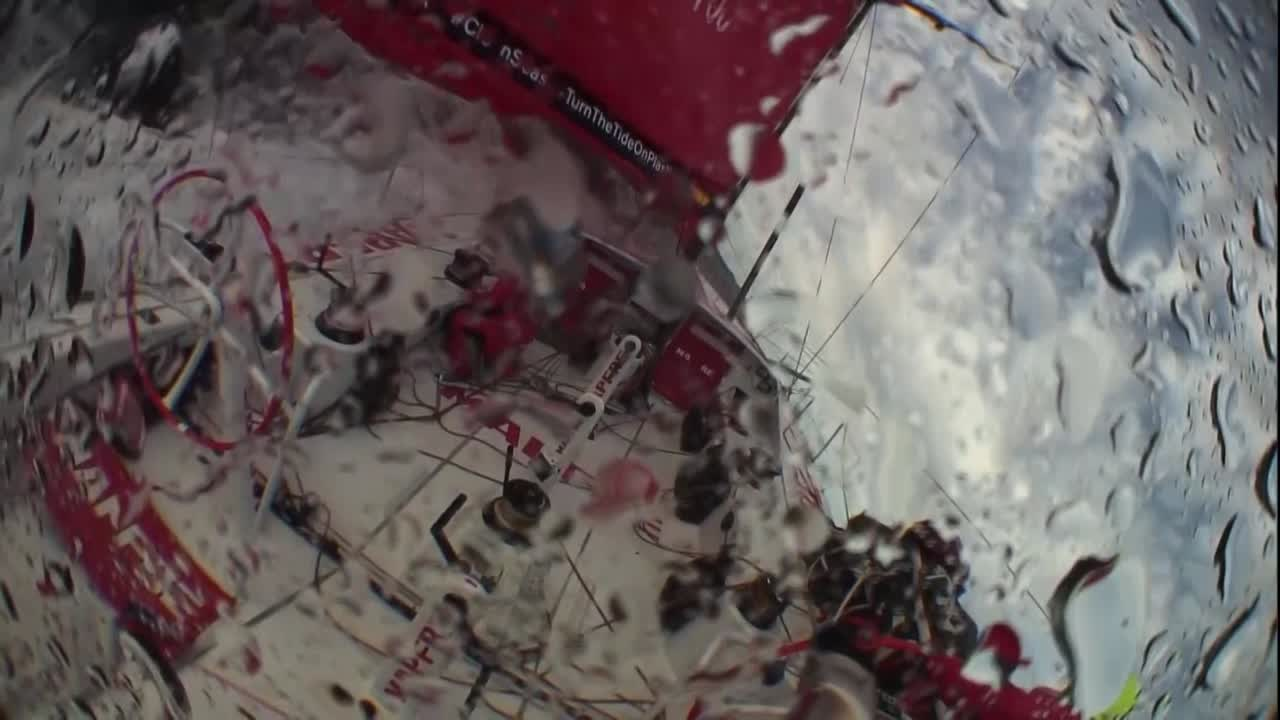 "Crash cam footage from the stern camera as MAPFRE rounds up to starboard in very strong winds. We see Louis run forward to ease the jib, then Blair comes forward and shelters in the weather side of the pit area. Rob (I think? by voice?) on the helm calls, ""Okay! I got it!"" as they start to come down, and Blair moves to the pedestal to grind the jib back in. (I think.)"