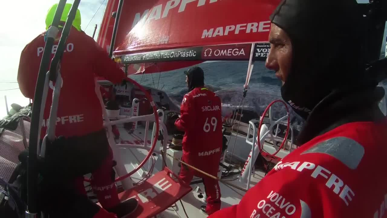 "MAPFRE is sailing downwind on port gybe. Pablo is steering, Louis is grinding, Blair is trimming. Blair squints into the sun. ""Where are they?"" Shot of Dongfeng crossing on starboard a few hundred yards astern of them. [Note: This might be a different time than the squinting; it's no overcast.] Blair talks to Jen about how this morning earlier they'd gone below after a gybe and heard them easing the sheets, poked his head up and say MAPFRE cross about 5 meters behind Dongfeng. Talks about giving a ""cheeky wave."" ""Since then there's been 3 or 4 crosses, and they're about a mile ahead now."" Slomo washing machine."