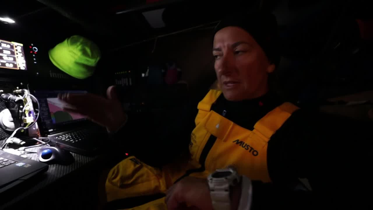 "Dee, at the nav station, explains about how the ice limit has been moved since they started racing, and the effect of that is that they have different wind conditions to sail in. ""To the north of us is a big high pressure, to the south is a barrier we can't quite cross, and it leaves us this very narrow corridor of breeze to sail in."" She explains this is her sixth time in the Southern Ocean, and she doesn't remember sailing this far north in this area. Doesn't think she's sailed north of the Kerguelen Islands before. Talks about climate change as a possible factor in pushing the ice further north. Harder work to sail this way, but better safety. Screenshot of the ice limit and Kerguelen Islands. Stacking. Francesca does the Twist to pull a stacking pole from the deck. Franchesca on the helm. Crew plays roshambo. Slomo washing machine over Bianca (I think) on the aft grinder pedestal."
