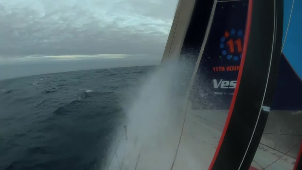 "Condensation dripping inside from a grab rail. Firehose shot of the foredeck while Vestas is triple-heading. SiFi, unrecognizable in his balaclava except by voice, talks about how they're now drag-racing, not gybing. ""We're starting to pin our ears back and sail fast."" On the stern, Tony talks about the current conditions. He asks the termperature; Stacey answers ""Nine and nine."" Tony explains: 9 degrees C air, 9 degrees water. He talks about how even with all the layers you get cold, but if you move you get hot and then sweat, and then you get wet and cold again. Tony talks about his 3-day-old protein bar he's found in his pocket and is going to eat. Stacey says she can do better: Pulls out a bar. ""Tropical holiday."""
