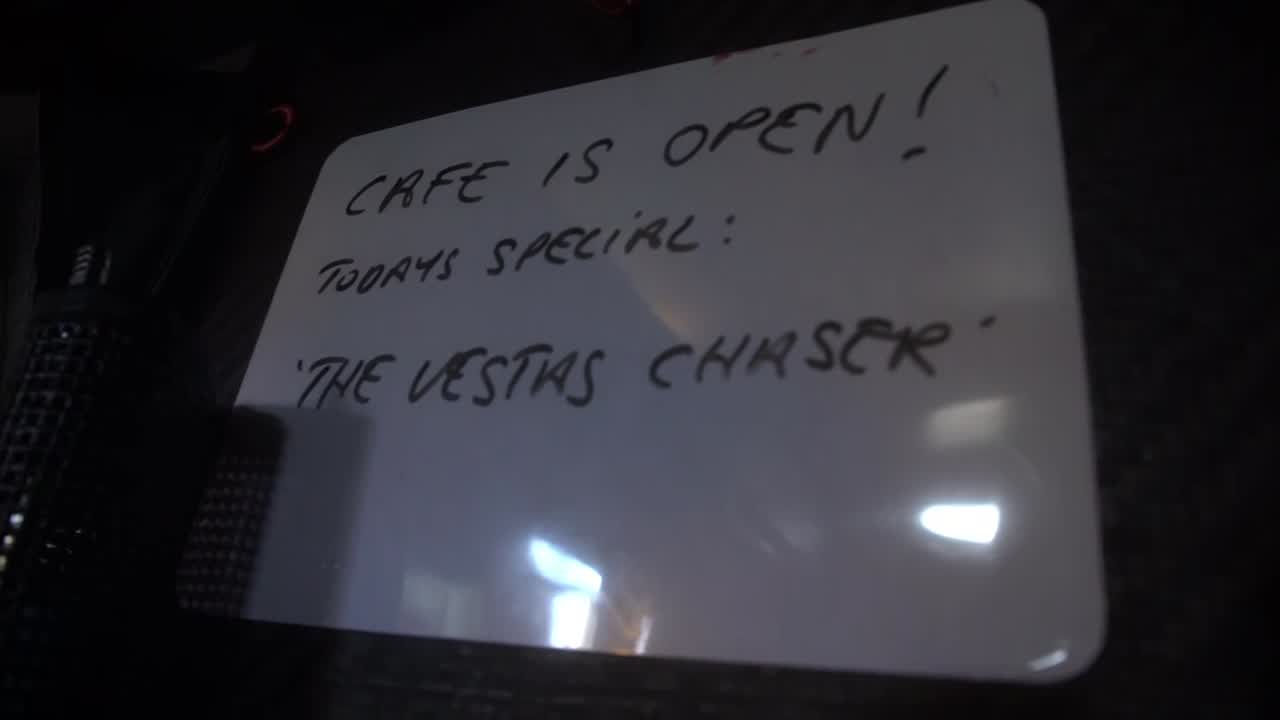 "Annie writes a sign on the whiteboard: ""CAFE IS OPEN! TODAYS SPECIAL: 'THE VESTAS CHASER'"". Annie in the galley preparing something. ""Feeling much better. Finally out of my bunk after 72 hours. It feels amazing. They've been really good. I feel like I have an email relationship with Spike now. We speak every 6 hours... I keep asking if I can push through the pain, and he doesn't like that... I think by lunchtime today I'm going to be negotiating on when I can go back on deck... At least I can make breakfast. Do something for the team, which feels good, because I've been watching them work for 3 days. Yesterday, at least I can make the meals, and clean a bit. If it helps the guys have more time in the their beds, hopefully it's helping a little bit."" She preps a meal in an insulated box. Talks with Abby. ""With gravy? I'll see what I can whip up."""